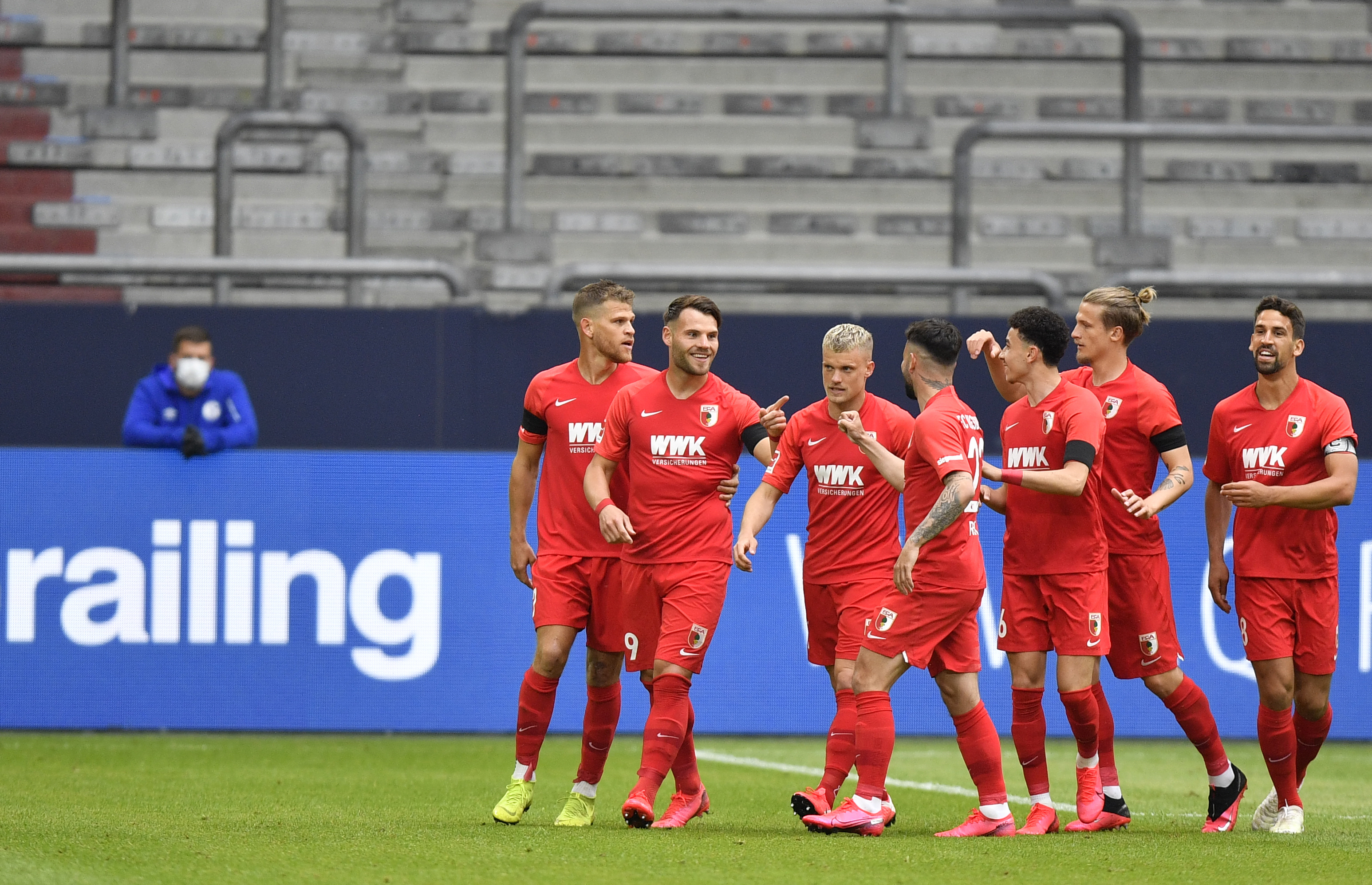 Augsburg's Eduard Loewen celebrates with teammates after scoring his side's opening goal during the German Bundesliga soccer match between FC Schalke 04 and FC Augsburg at the Veltins-Arena in Gelsenkirchen, Germany, Sunday, May 24, 2020. The German Bundesliga becomes the world's first major soccer league to resume after a two-month suspension because of the coronavirus pandemic. (AP Photo/Martin Meissner, Pool)