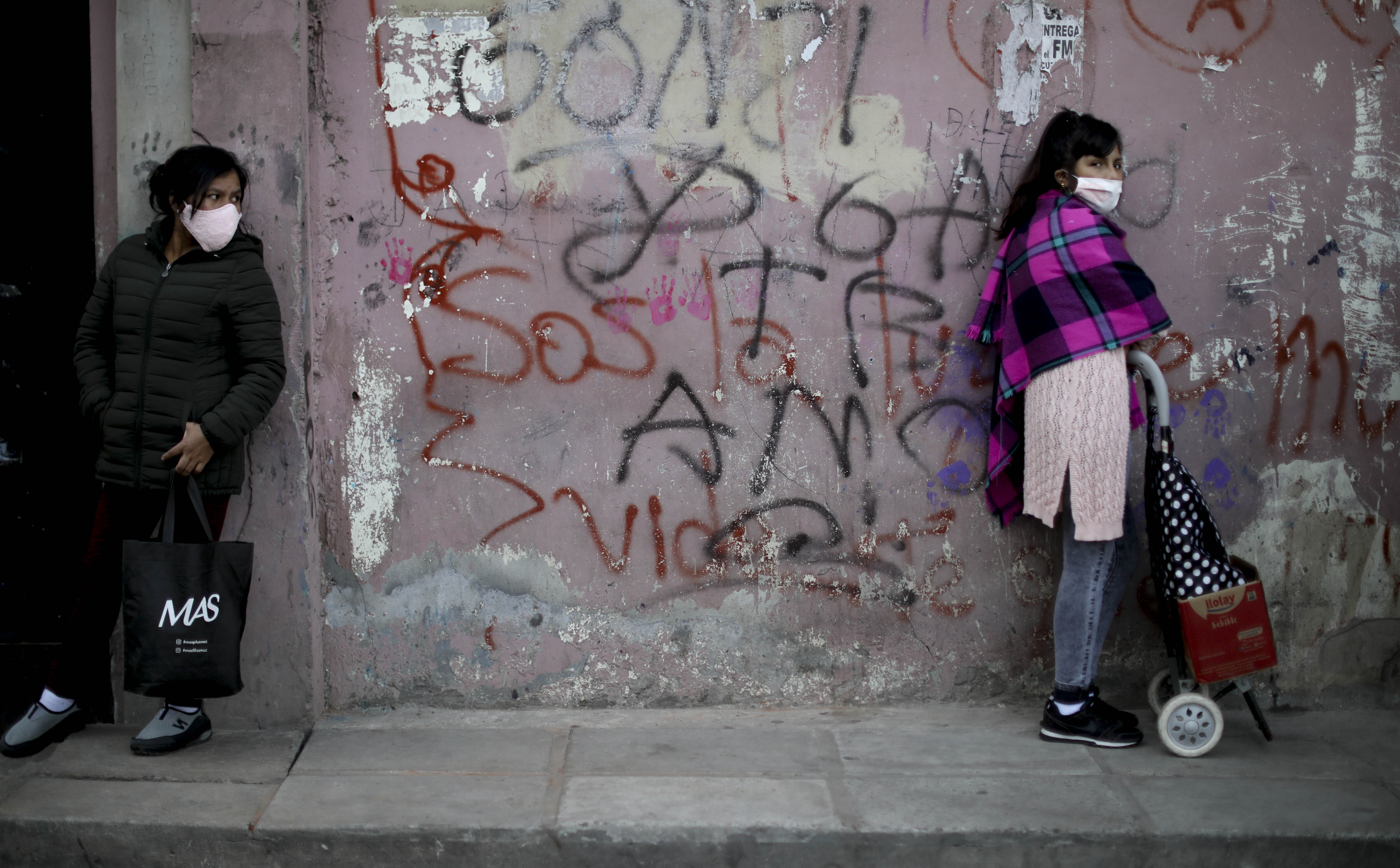 Women stand at a distance as they wait in line for a plate of food at a soup kitchen in the 1.11.14 neighborhood during a government-ordered lockdown to curb the spread of the coronavirus in Buenos Aires, Argentina, Friday, May 29, 2020. (AP Photo/Natacha Pisarenko)