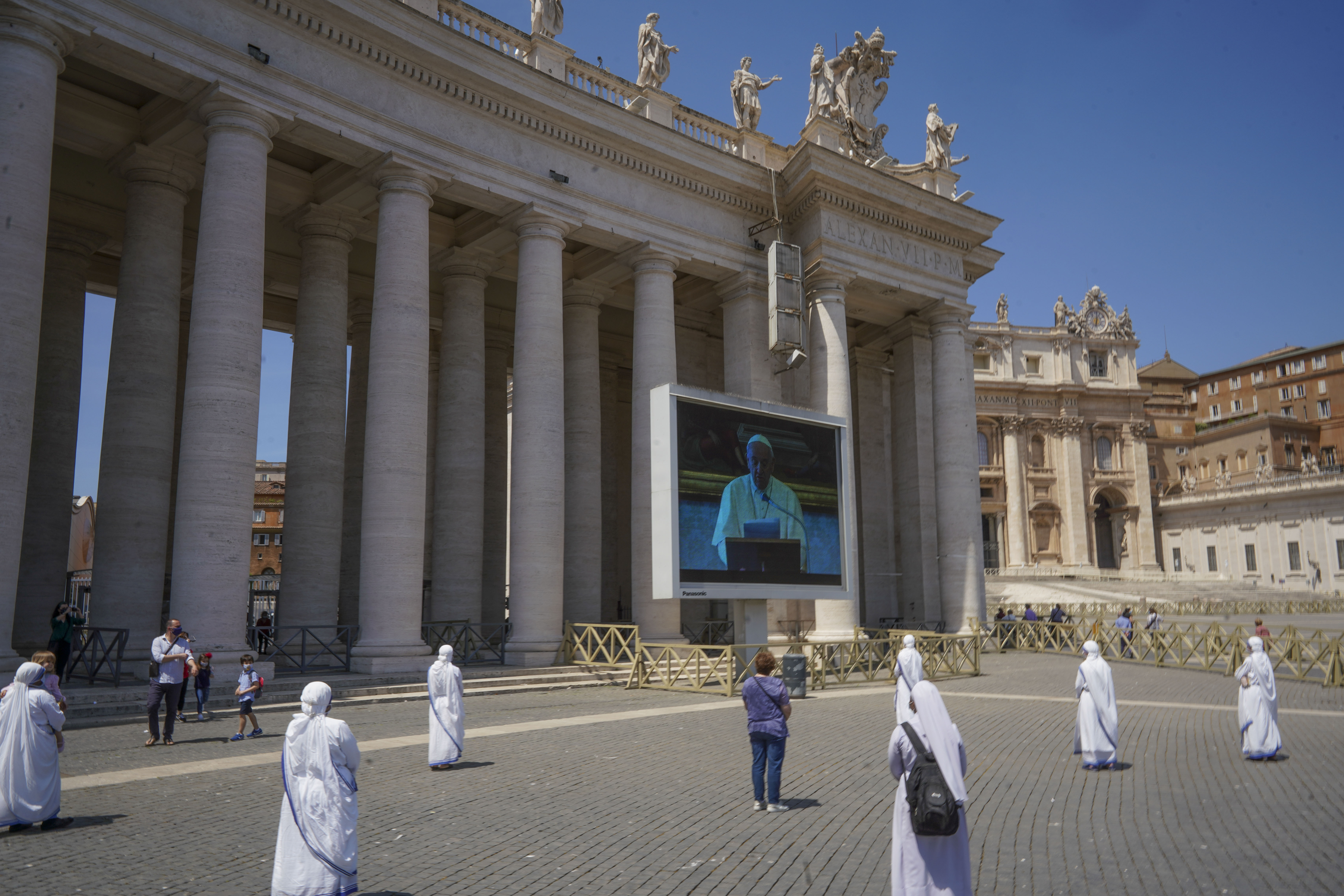 Nuns and faithful respecting social distancing look at Pope Francis reciting the Regina Coeli noon prayer on a giant screen in St. Peter's Square, at the Vatican, Sunday, May 24, 2020. For the first time in months, well-spaced faithful gathered in St. Peter's Square for the traditional Sunday papal blessing, casting their gaze at the window where the pope normally addresses the faithful, since the square had been closed due to anti-coronavirus lockdown measures.  (AP Photo/Andrew Medichini)