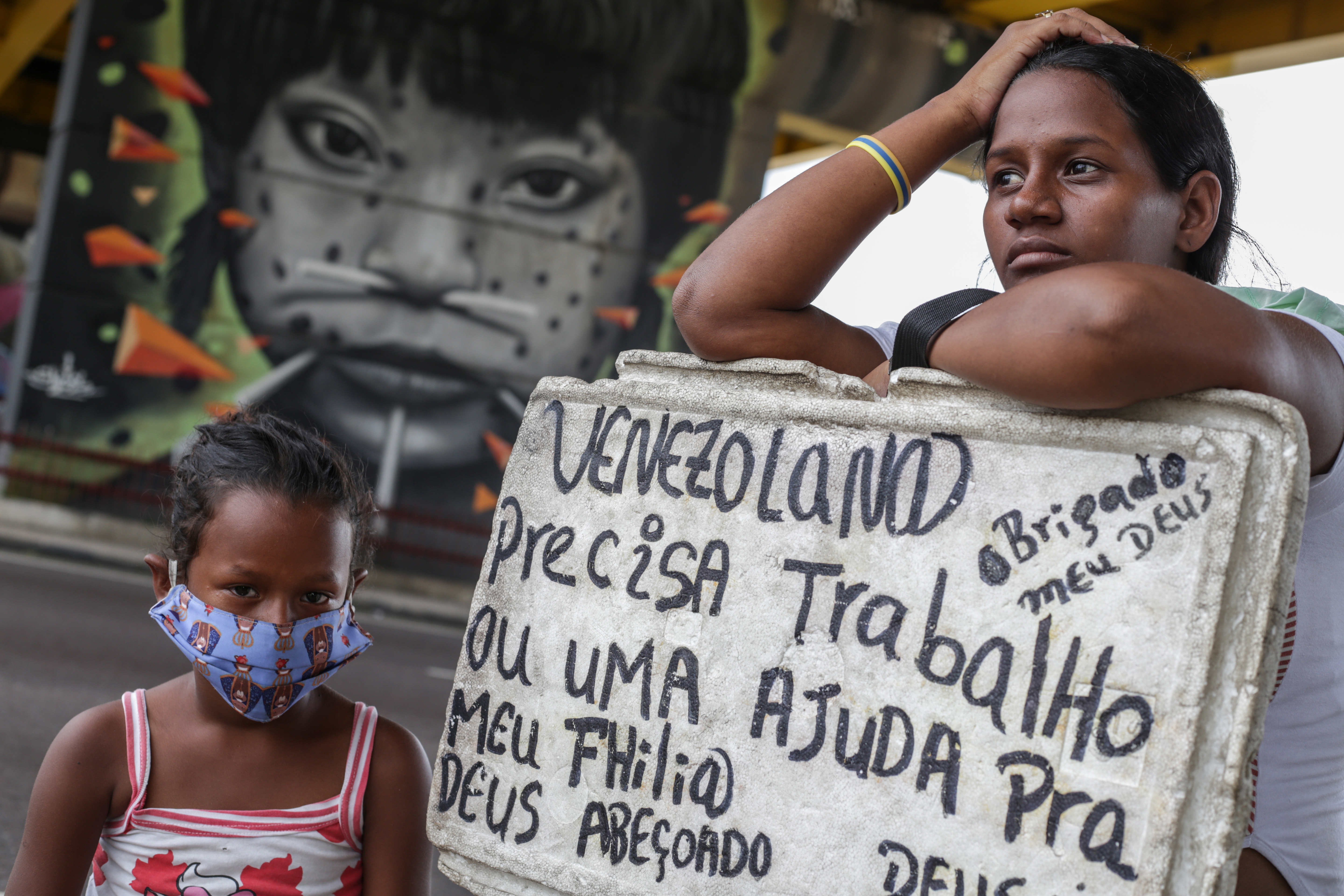 MANAUS, BRAZIL - MAY 23: Melida Marquez, a 23 years old venezuelan woman holds a sign asking for job and help with her daughter Genesis, 6, at downtown Manaus on May 23 2020 in Manaus, Brazil. Melida arrived in Manaus a year ago, is pregnant of her fourth kid and has no protective masks. She uses the money  got from pedestrians to buy food for her family. Brazil has now 330.890 people infected by the coronavirus disease (COVID-19) according to Health Ministry and became the the second country in the world with more cases. (Photo by Andre Coelho/Getty Images)
