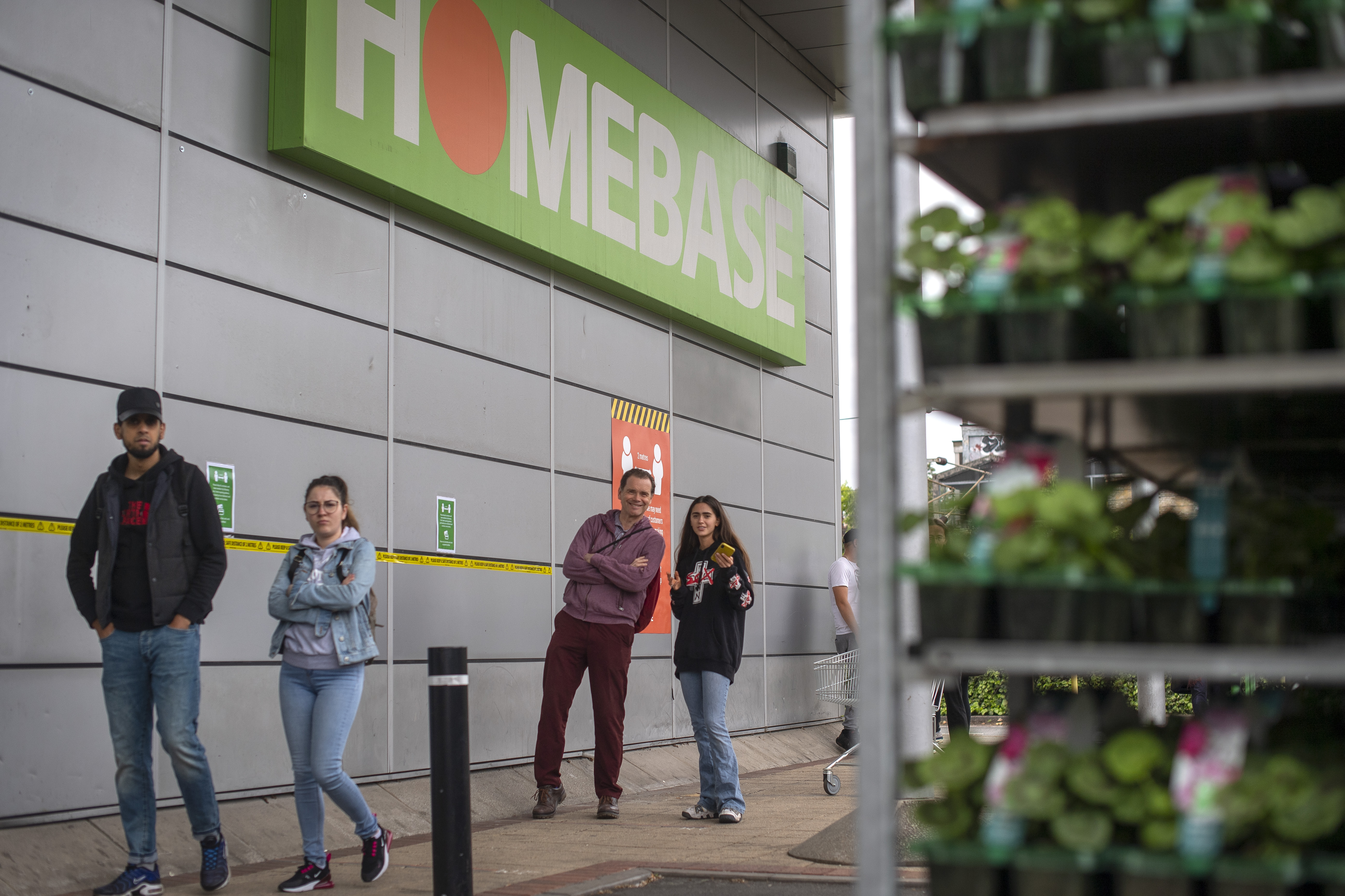 Customers maintain social distancing in a queue to enter a Homebase store in north London, as the UK continues in lockdown to help curb the spread of the coronavirus.
