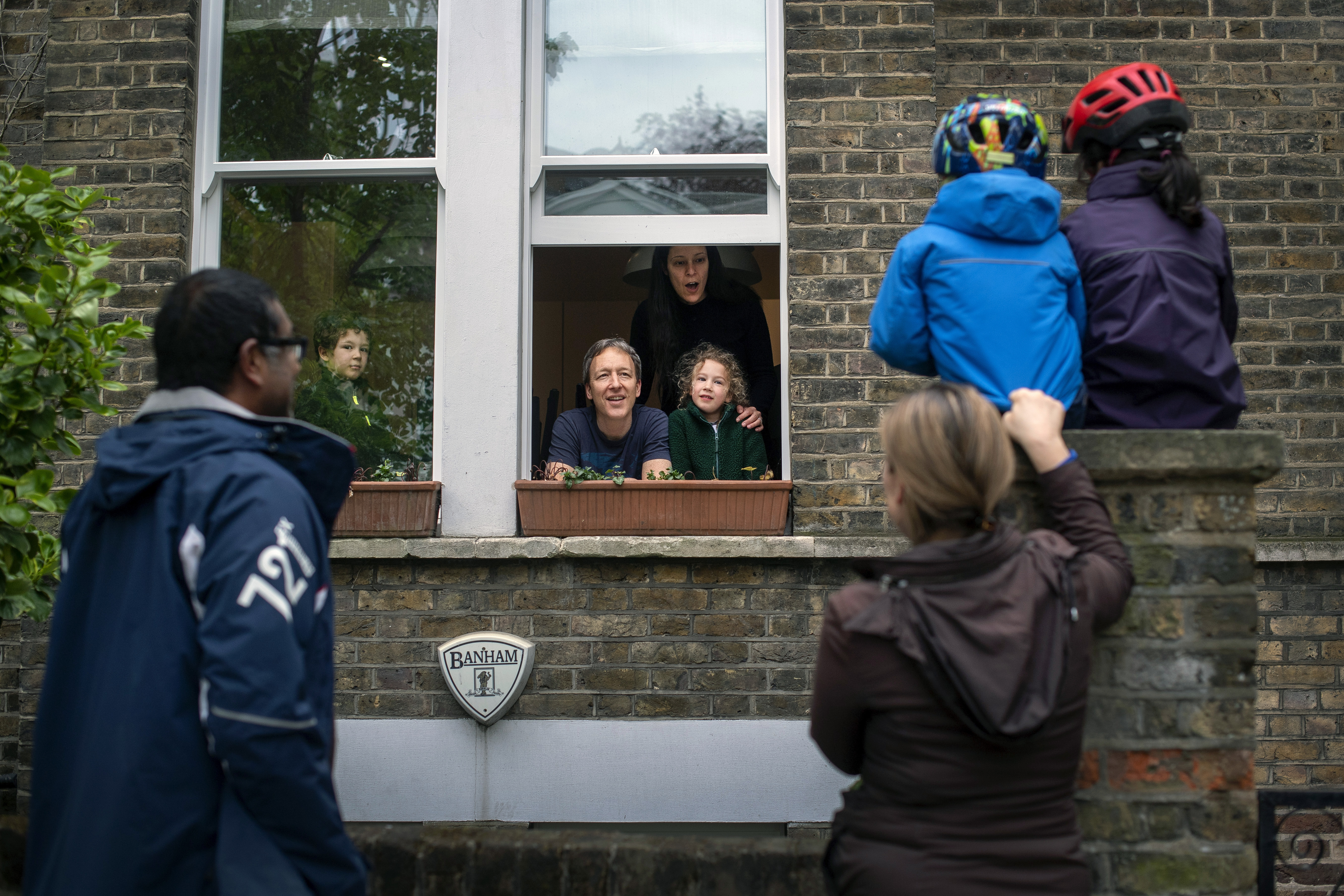 **Parental permission granted** Two families maintain social distancing while talking to each other outside a home in Hampstead, north London, as the UK continues in lockdown to help curb the spread of the coronavirus.