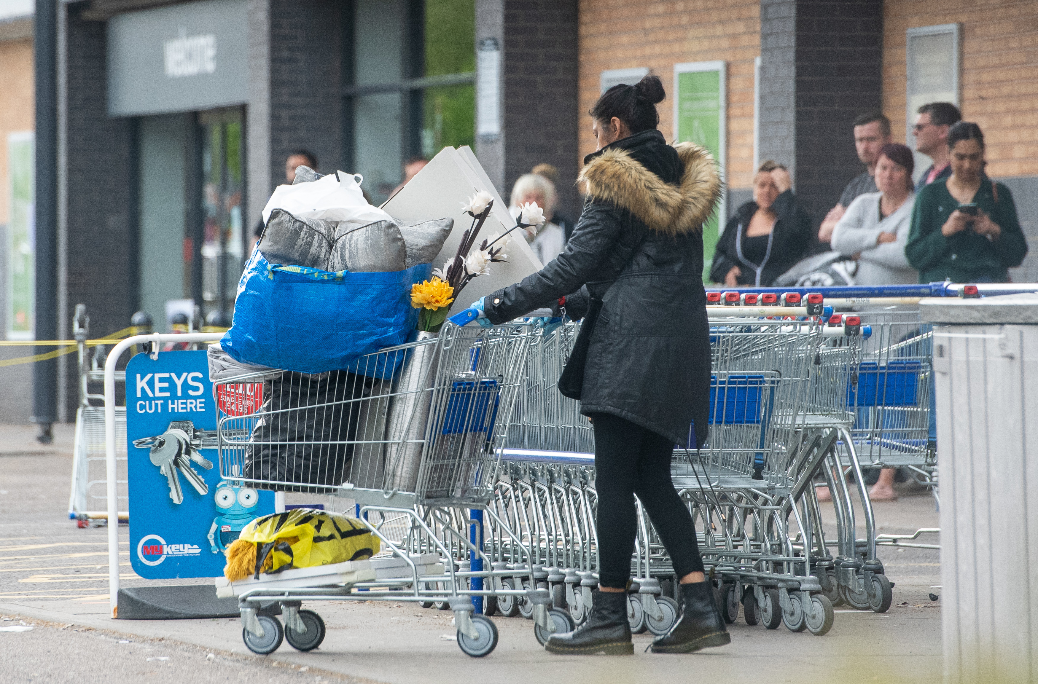 A woman pushes a trolley away from The Range in Leicester as the UK continues in lockdown to help curb the spread of the coronavirus.