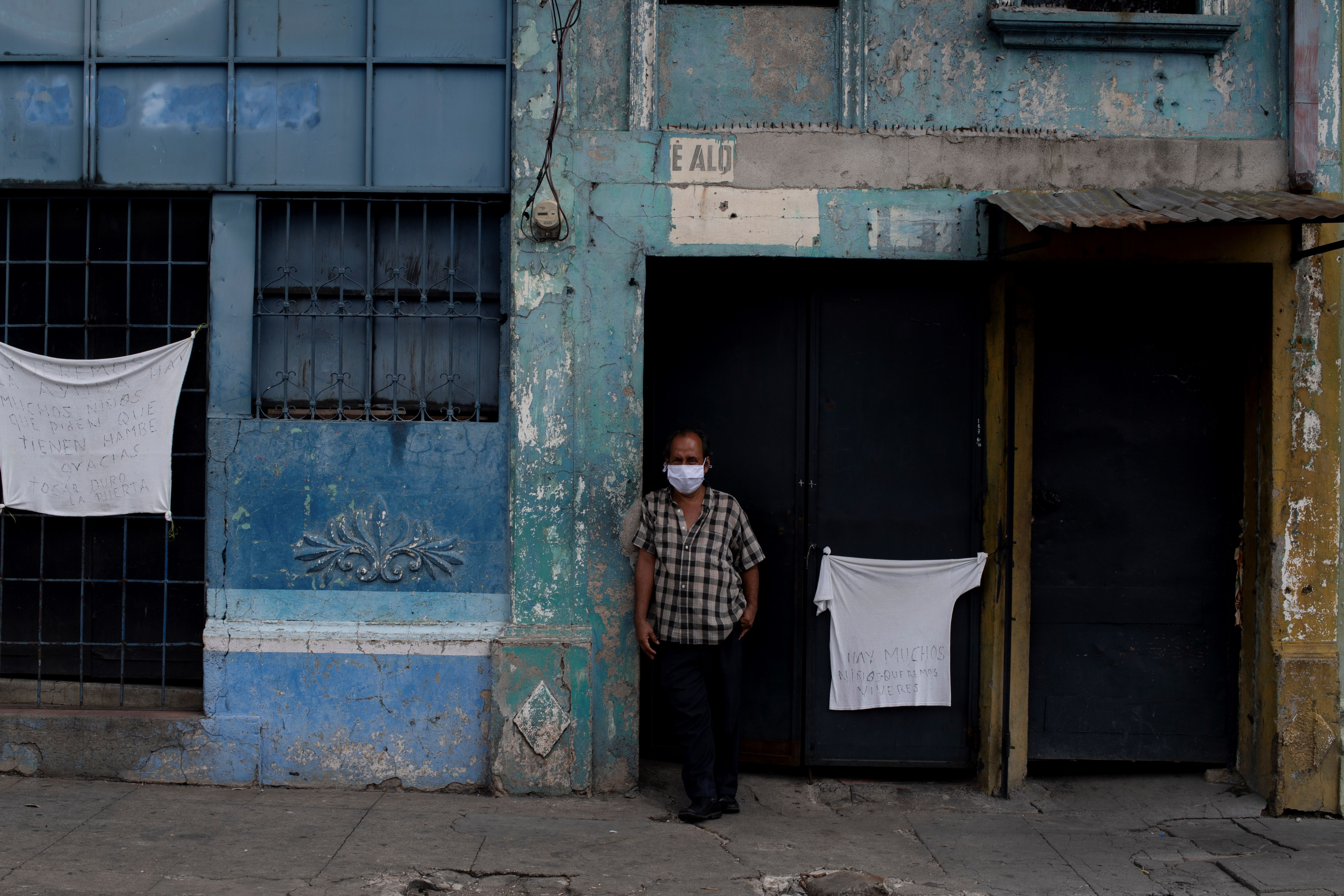 A man stands outside his house, flanked by white cloths displayed to demand humanitarian aid during the home quarantine against the spread of the novel COVID-19 coronavirus, at Concepcion neighborhood in San Salvador on May 23, 2020. - El Salvador's Supreme Court of Justice (CSJ) revalidated on the eve the state of emergency decree -in force since last March- to face the COVID-19 pandemic, after intervening in a legal battle between the Legislative Assembly and the government of President Nayik Bukele. (Photo by Yuri CORTEZ / AFP) (Photo by YURI CORTEZ/AFP via Getty Images)