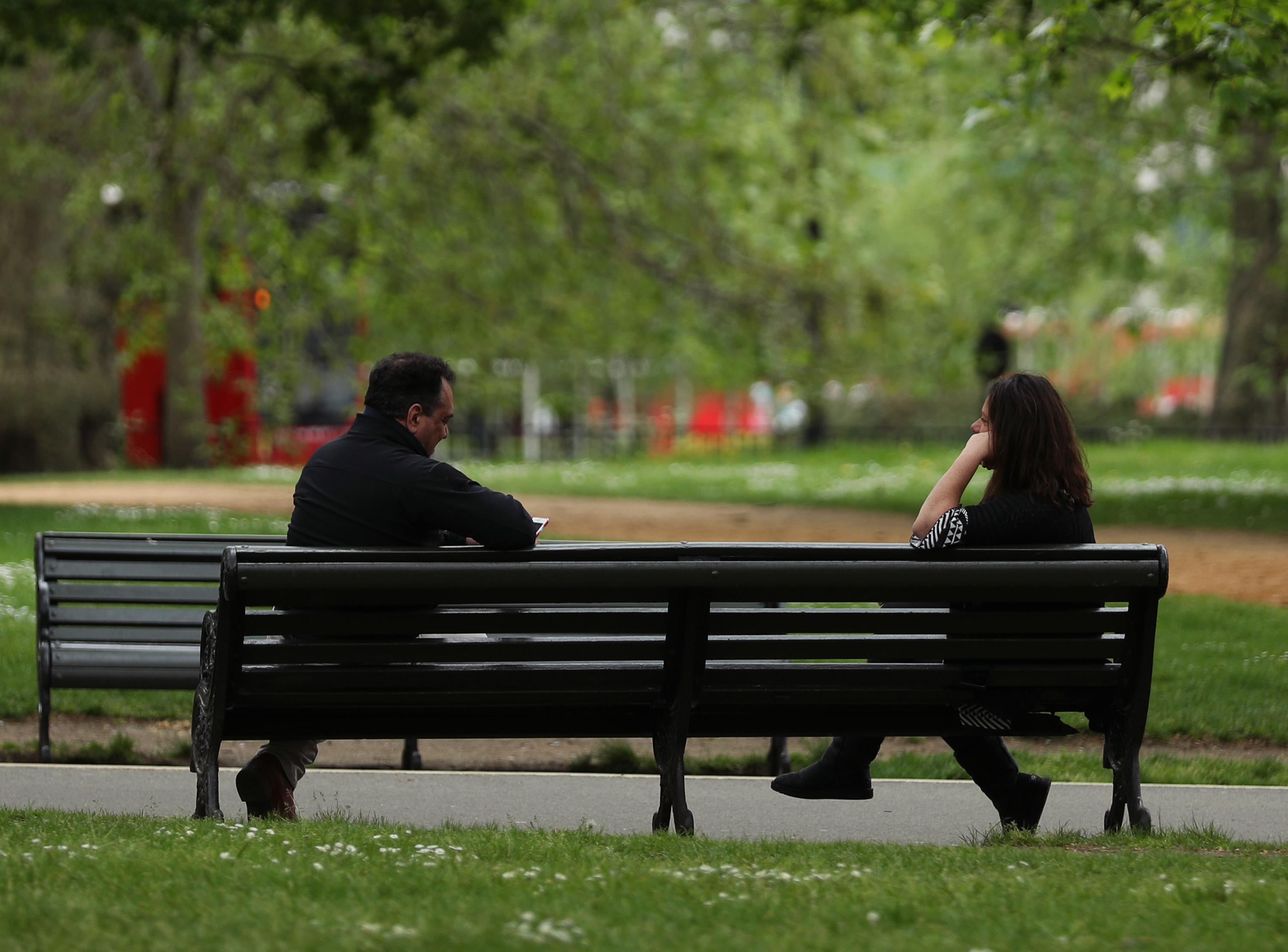 People observing social distancing on a bench in Hyde Park, London, as the UK continues in lockdown to help curb the spread of the coronavirus.