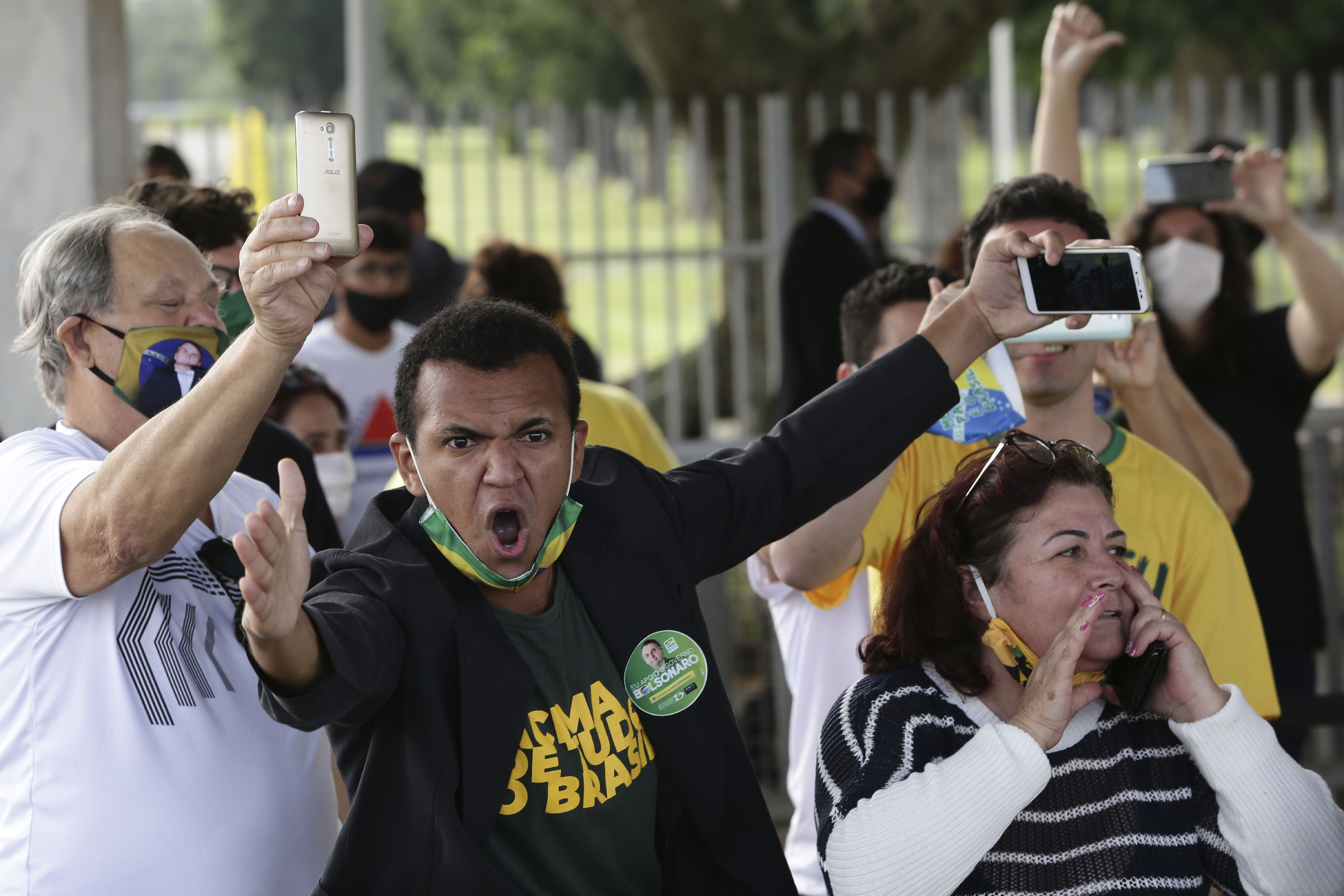 """Supporters of Brazil's President Jair Bolsonaro, wearing face masks amid the new coronavirus pandemic, yell out against journalists, calling them """"trash"""" and """"coup plotters,"""" after the president's departure from his official residence of Alvorada palace in Brasilia, Brazil, Monday, May 25, 2020. (AP Photo/Eraldo Peres)"""