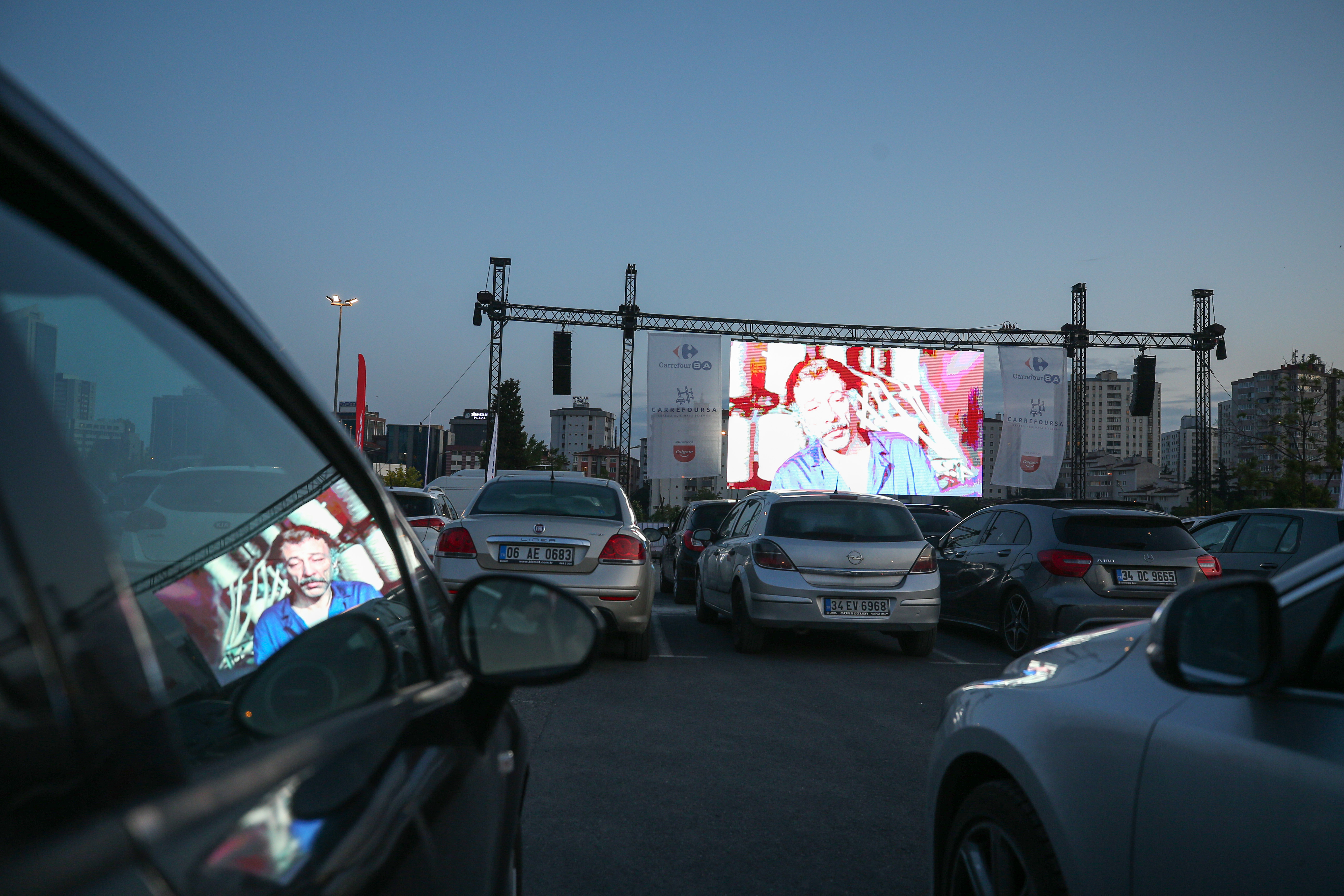 """ISTANBUL, TURKEY - MAY 28: A view of cars during drive-in-theatre amid coronavirus (Covid-19) pandemic organized by CarrefourSA in Istanbul, Turkey on May 28, 2020. The Turkish movie """"Our Family"""" was screened on the theatre. (Photo by Muhammed Enes Yildirim/Anadolu Agency via Getty Images)"""