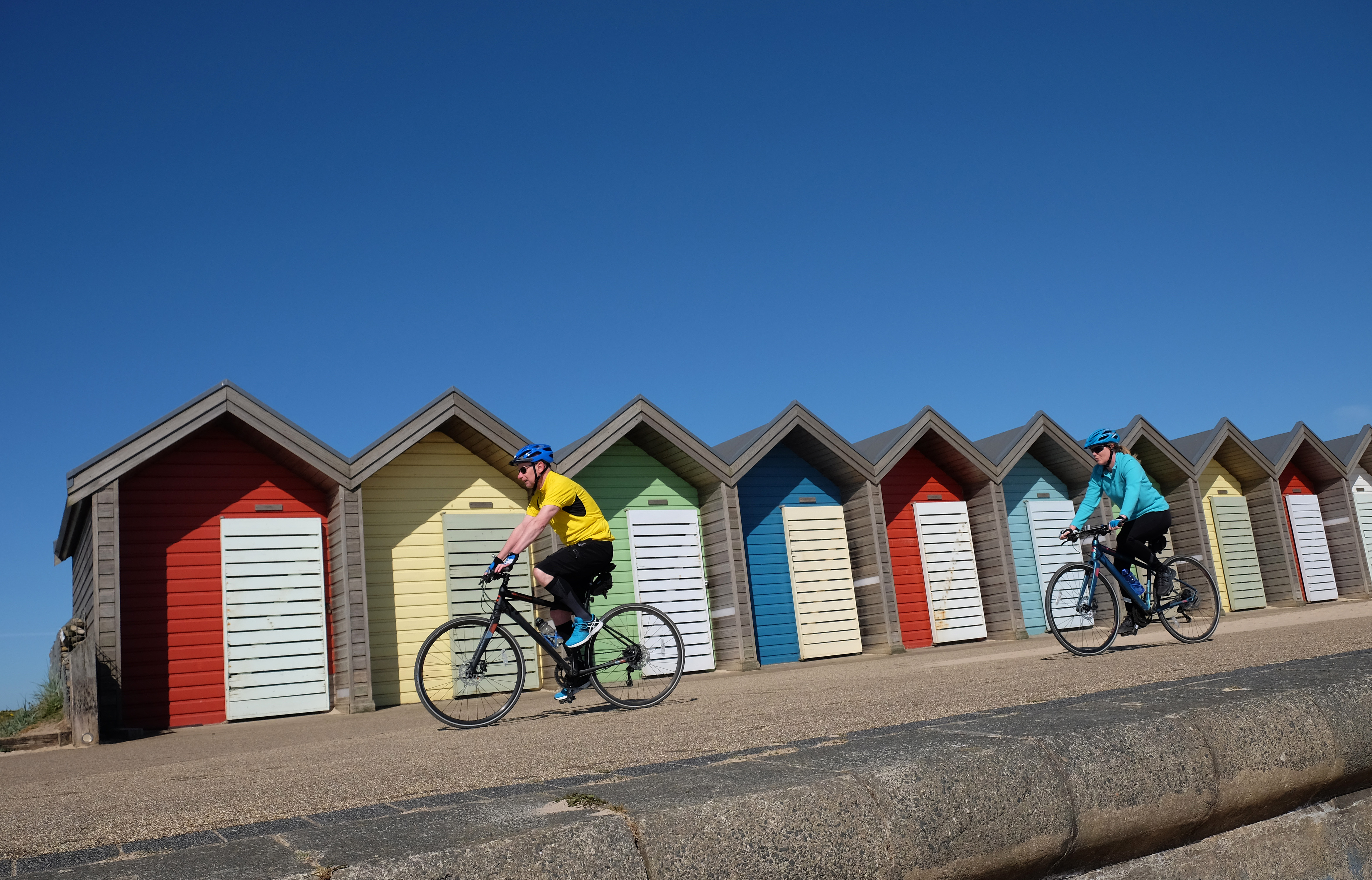 Cyclists ride under a clear blue sky in Blyth, Northumberland, as highs of 22C are now expected for some parts of the UK by the weekend.