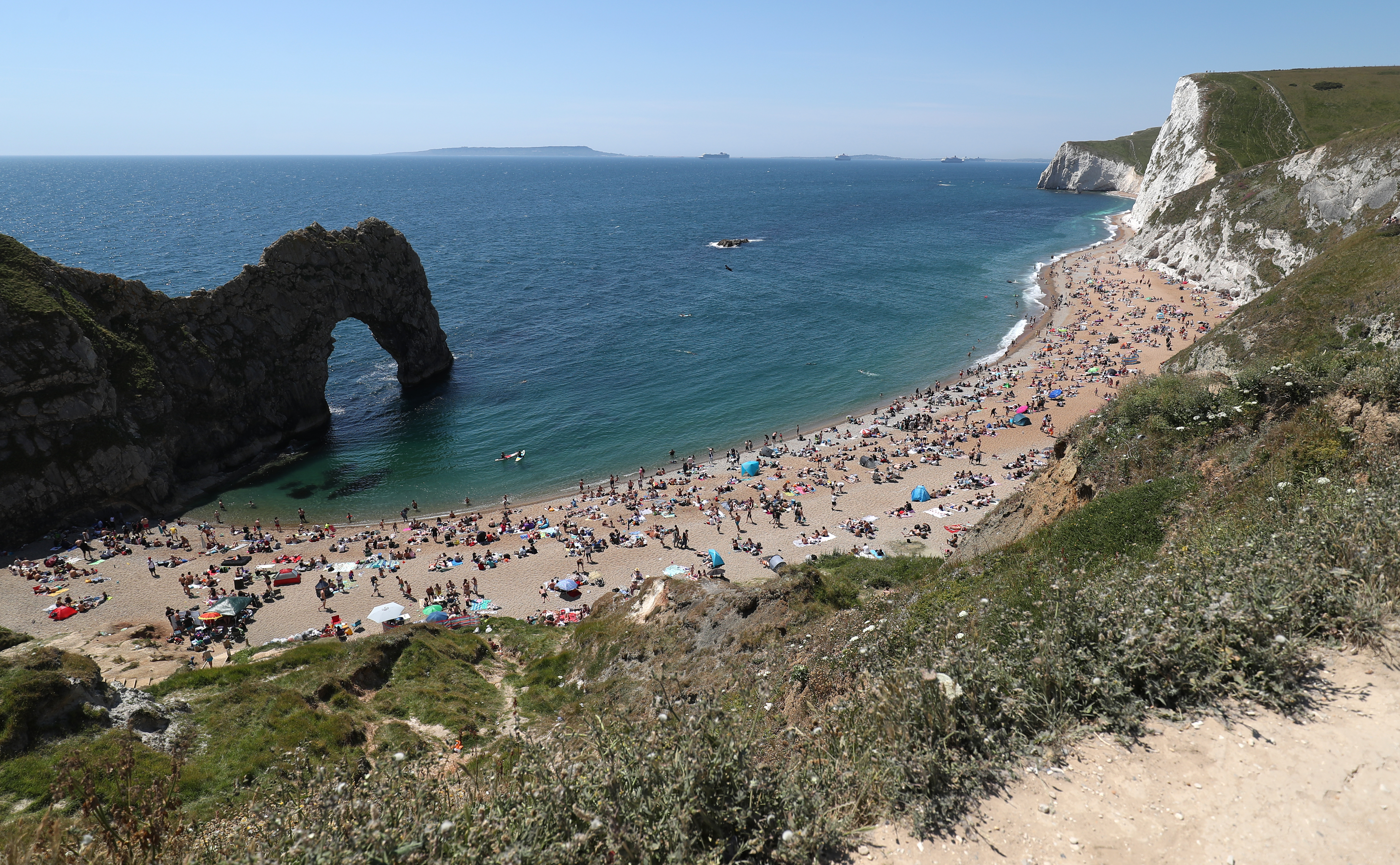People fill the beach at Durdle Door, near Lulworth, despite Dorset Council announcing that the beach was closed to the public after three people were seriously injured jumping off cliffs into the sea.