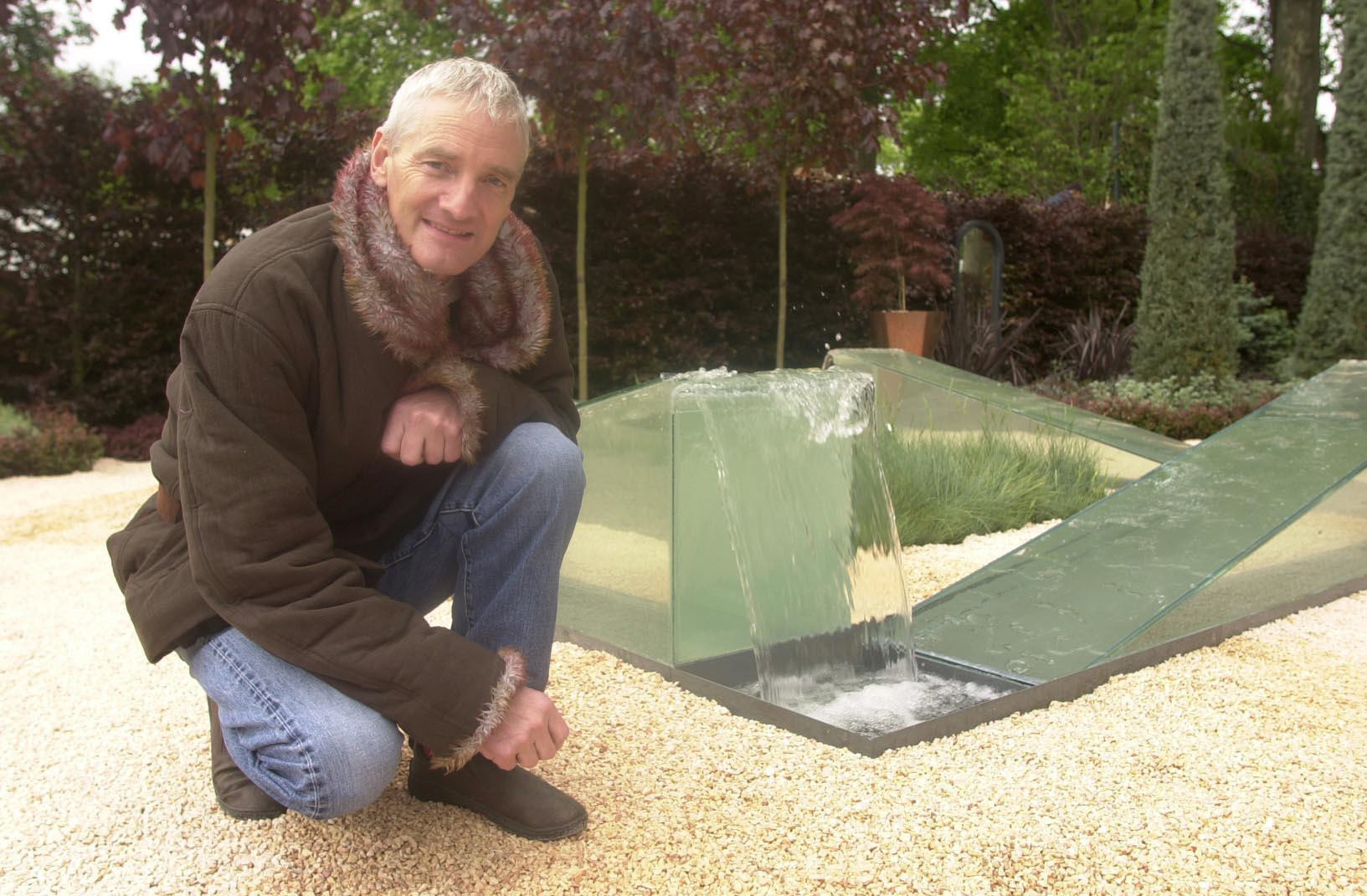James Dyson crouches besides part of his 'The Wrong Garden' on display at the 2003 Chelsea Flower Show held in central London, that he designed with the help of Jim Honey. The garden's focal point is James's water fountain where water appears to flow upwards.  * The Chelsea Flower Show is held in the grounds of the Royal Hospital, Chelsea, and opens to Royal Horticultural Society (RHS) members on Tuesday and to the general public on Wednesday afternoon.