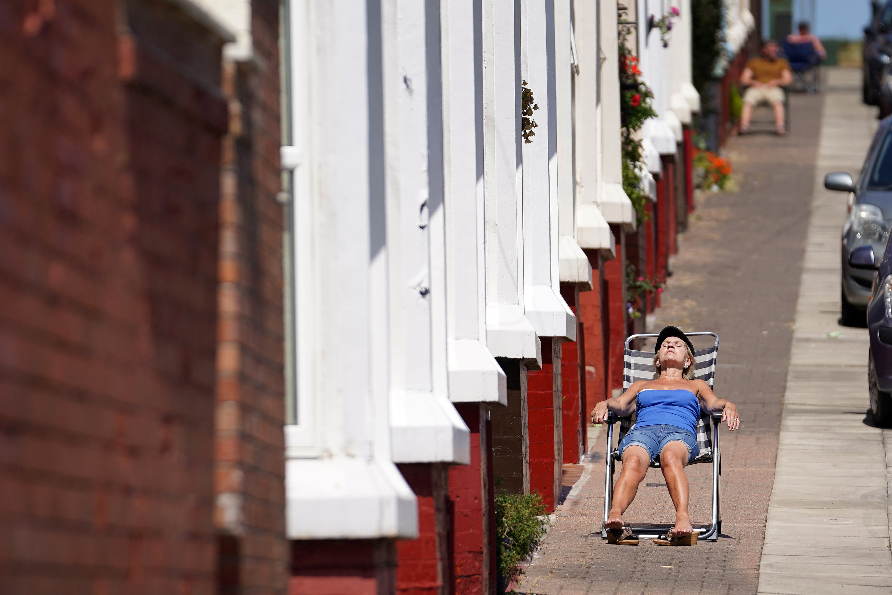 LIVERPOOL, UNITED KINGDOM - MAY 28: People enjoy the warm and sunny weather relaxing on the pavement outside their homes in the Shorefields area of Liverpool during the Coronavirus pandemic lockdown on May 28, 2020 in Liverpool, United Kingdom. The British government continues to ease the coronavirus lockdown by announcing schools will open to reception year pupils plus years one and six from June 1st. Open-air markets and car showrooms can also open from the same date.  (Photo by Christopher Furlong/Getty Images)