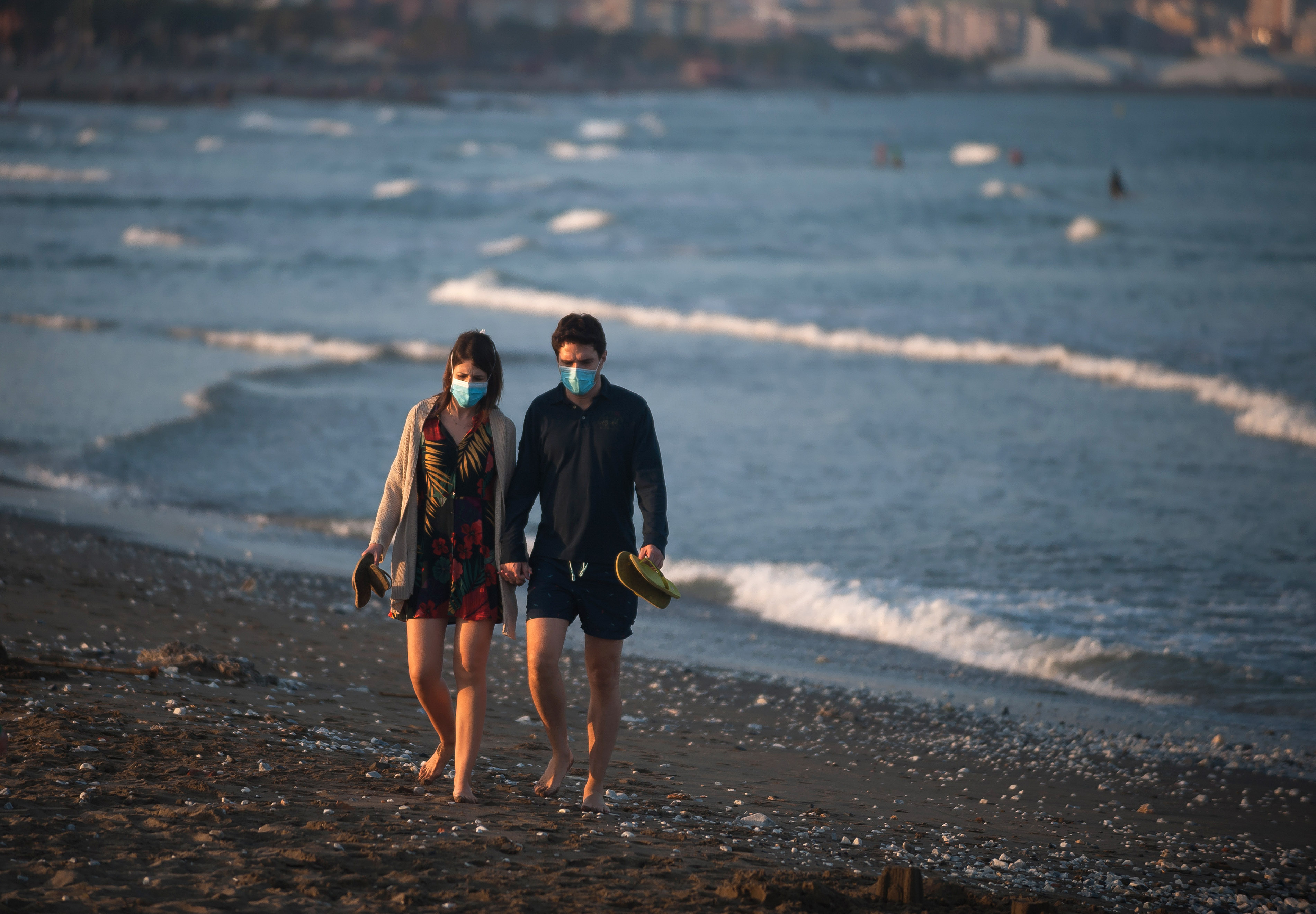 Una pareja camina por la playa usando mascarillas