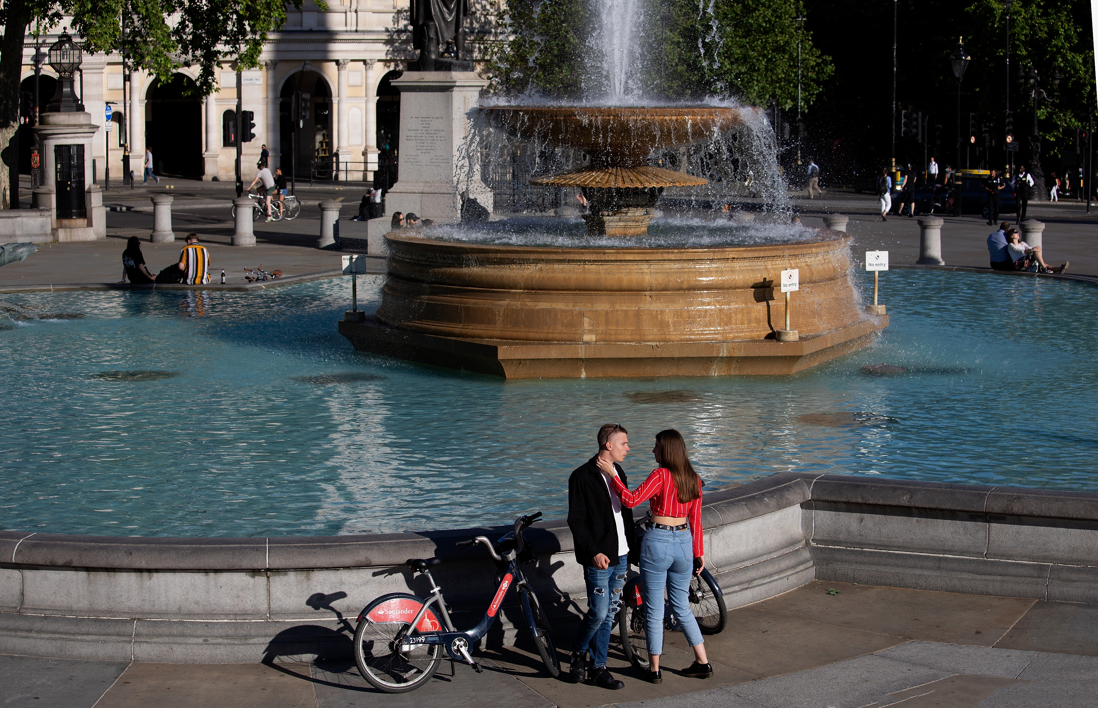 LONDON, ENGLAND - MAY 29: A couple with cycles meet in front of a fountain in Trafalgar Square during warm sunny weather on May 29, 2020 in London. The British government continues to ease the coronavirus lockdown by announcing schools will open to reception year pupils plus years one and six from June 1st. Open-air markets and car showrooms can also open from the same date.  (Photo by Jo Hale/Getty Images)