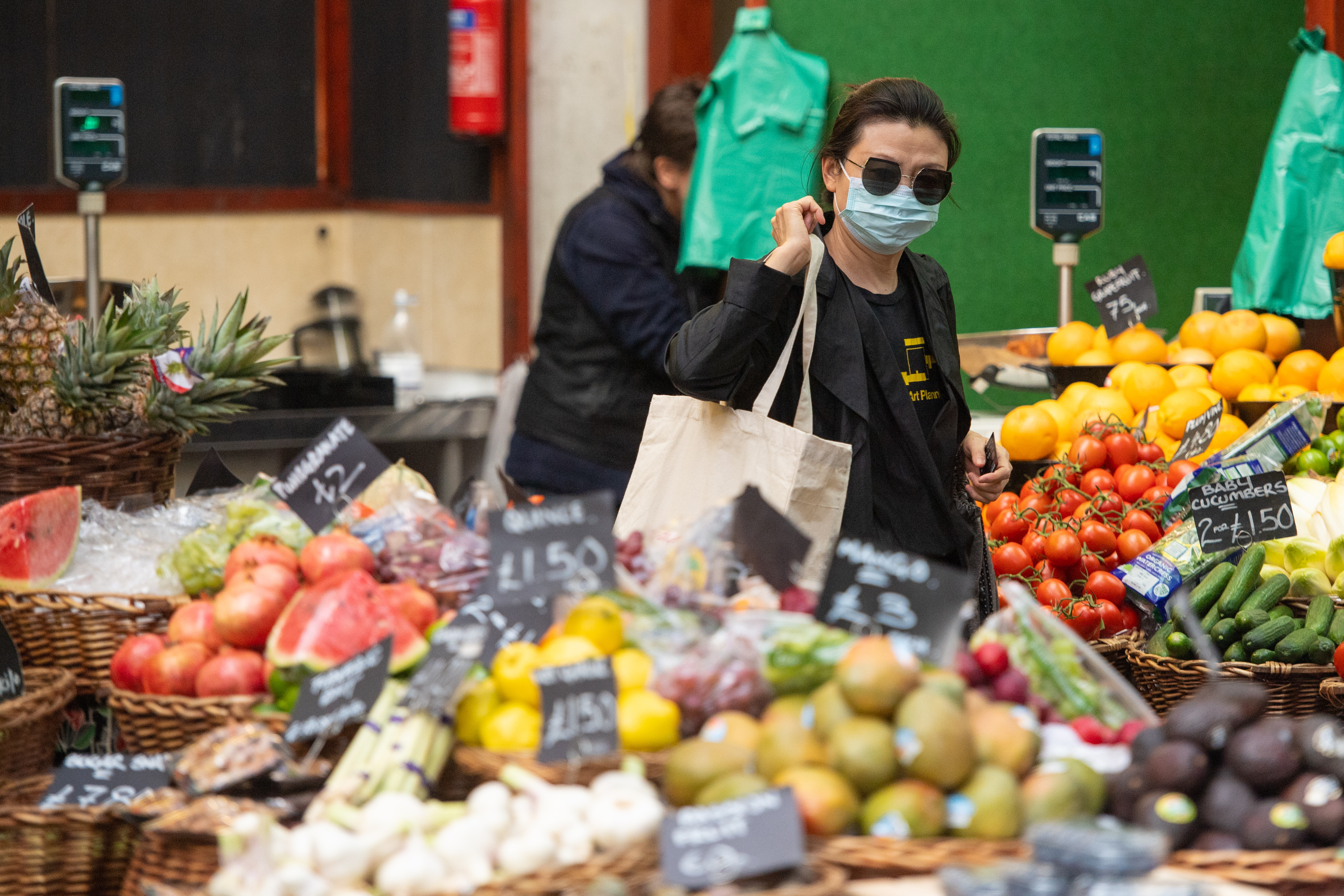 A shopper wearing a protective face mask at Borough Market, in London, following the introduction of measures to bring England out of lockdown. (Photo by Dominic Lipinski/PA Images via Getty Images)
