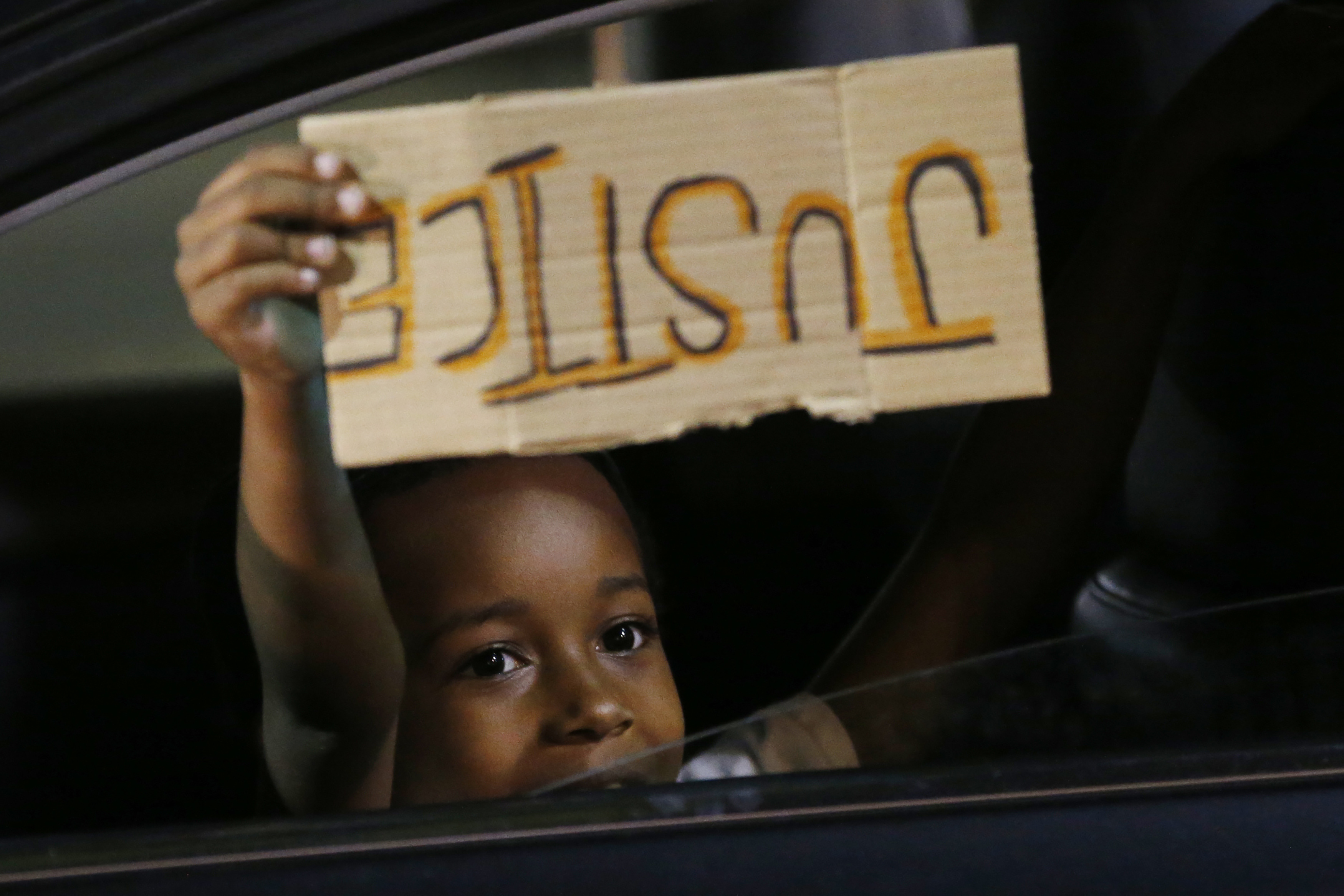 """A young boy holds a """"Justice"""" sign as he peers outside the window of a car passing protesters marching through downtown for a third night of unrest Sunday May 31, 2020, in Richmond, Va. Gov. Ralph Northam issued a curfew for this evening. (AP Photo/Steve Helber)"""