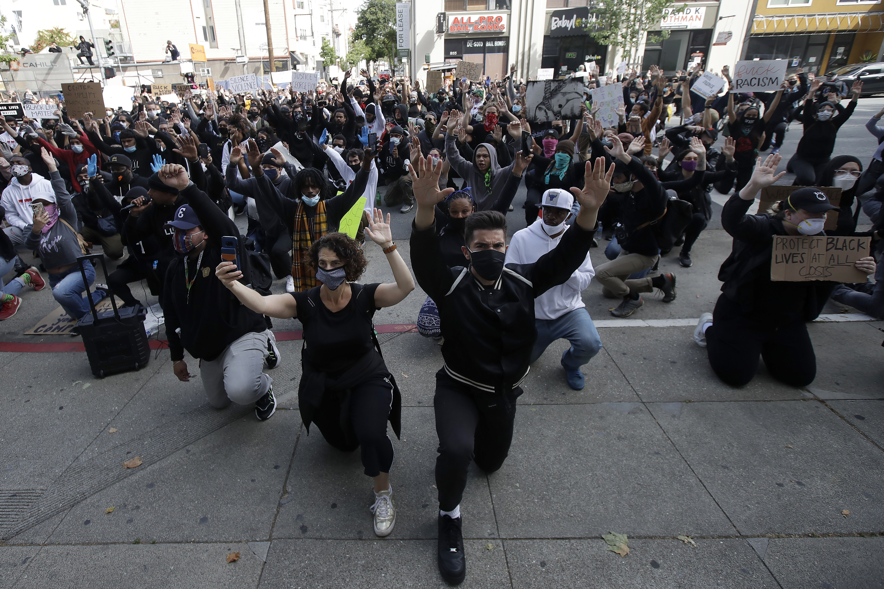 People kneel in front of the Hall of Justice in San Francisco, Sunday, May 31, 2020, at protests over the Memorial Day death of George Floyd. Floyd was a black man who was killed in police custody in Minneapolis on May 25. (AP Photo/Jeff Chiu)