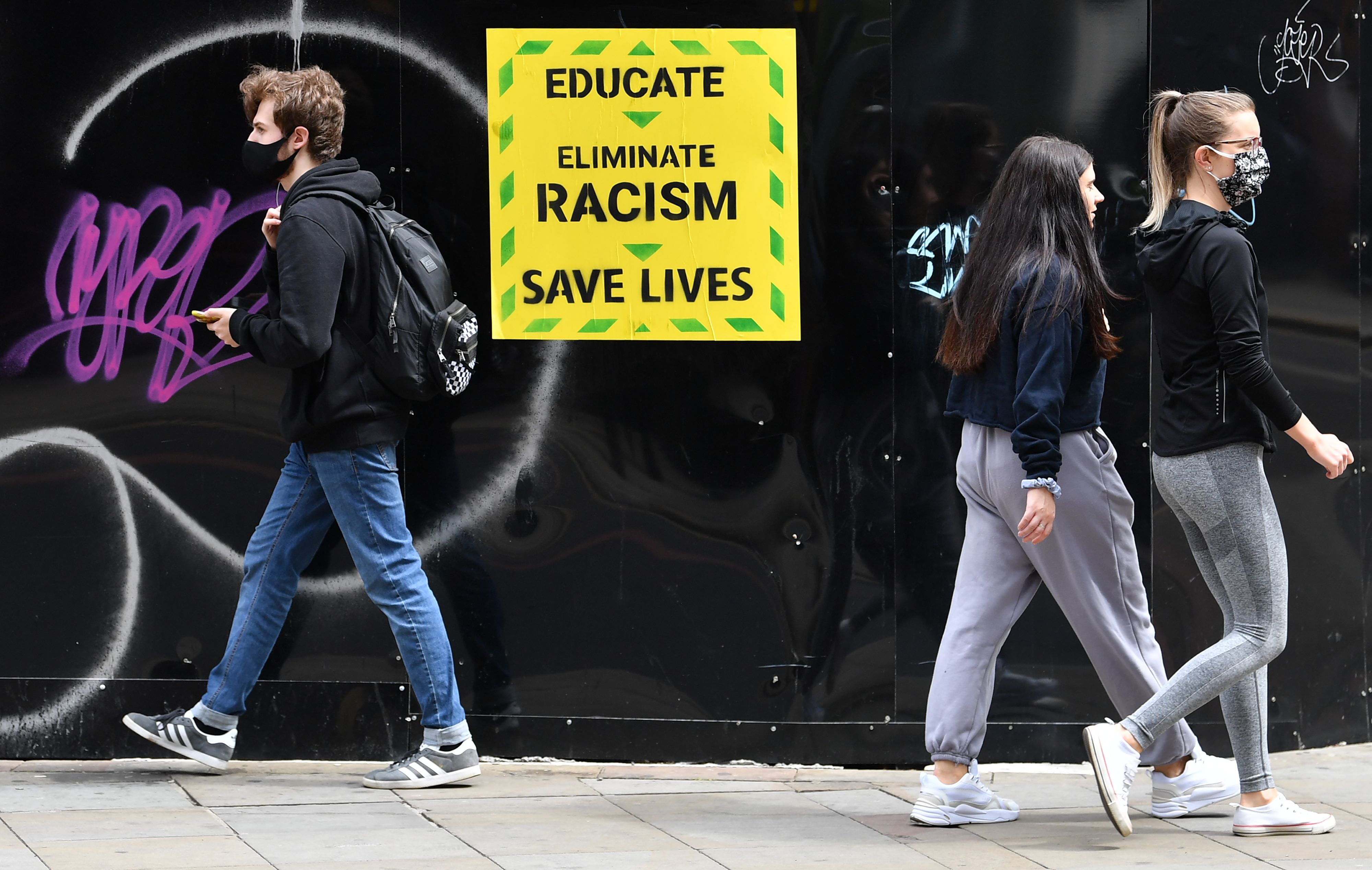 """Pedestrians wearing PPE (personal protective equipment), including a face mask as a precautionary measure against COVID-19, walk past an anti-racism poster in the them of the British government's Coronavirus slogan, near a demonstration in Manchester, northern England, on June 6, 2020, to show solidarity with the Black Lives Matter movement in the wake of the killing of George Floyd, an unarmed black man who died after a police officer knelt on his neck in Minneapolis. - The United States braced Friday for massive weekend protests against racism and police brutality, as outrage soared over the latest law enforcement abuses against demonstrators that were caught on camera. With protests over last week's police killing of George Floyd, an unarmed black man, surging into a second weekend, President Donald Trump sparked fresh controversy by saying it was a """"great day"""" for Floyd. (Photo by Paul ELLIS / AFP) (Photo by PAUL ELLIS/AFP via Getty Images)"""