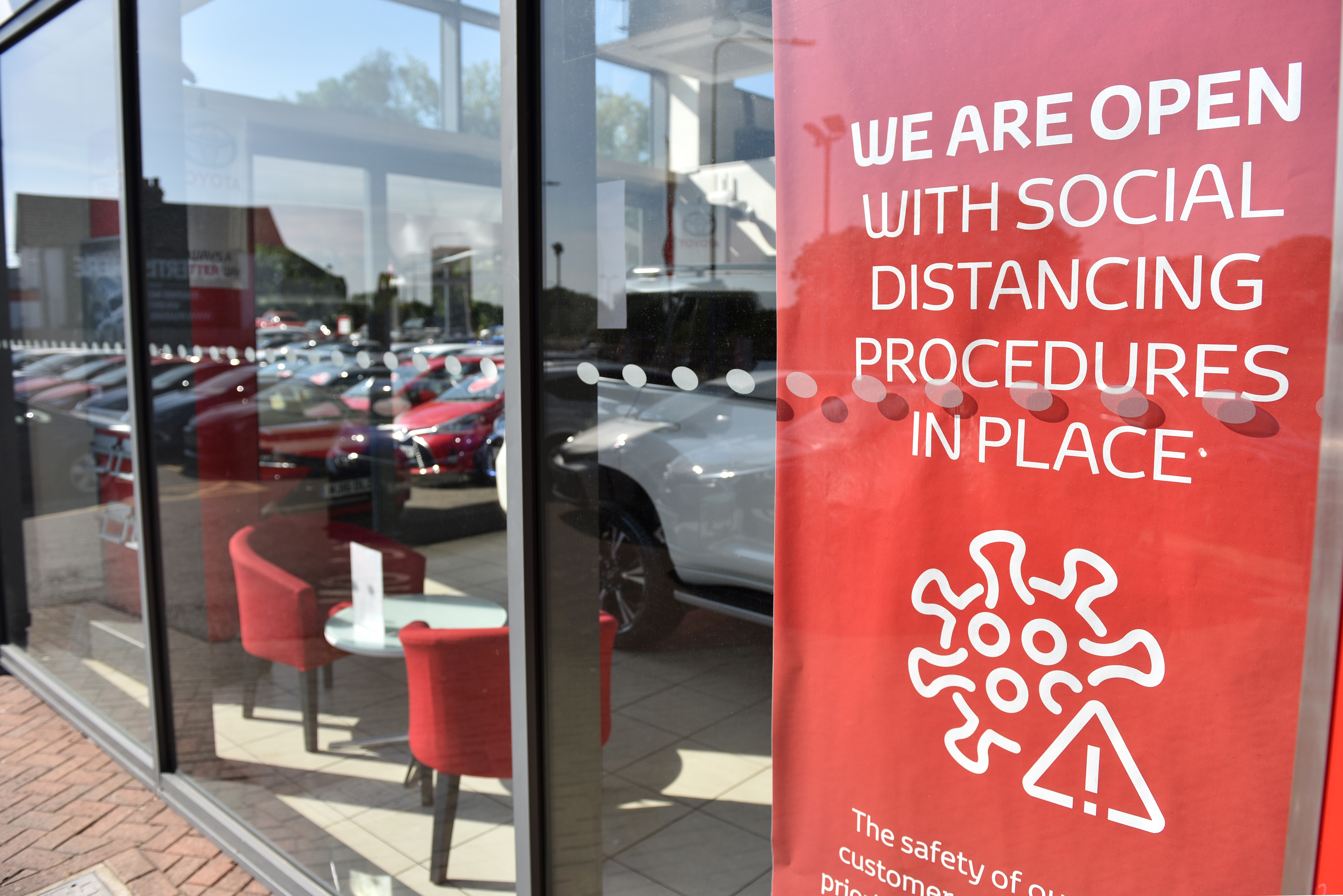 RAYLEIGH, ENGLAND - JUNE 01: Signs with social distancing guidelines in the window of a reopened Toyota car dealership showroom on June 01, 2020 in Rayleigh, England. The British government further relaxed Covid-19 quarantine measures in England this week, allowing groups of six people from different households to meet in parks and gardens, subject to social distancing rules. Many schools also reopened and vulnerable people who are shielding in their homes are allowed to go outside again. (Photo by John Keeble/Getty Images)