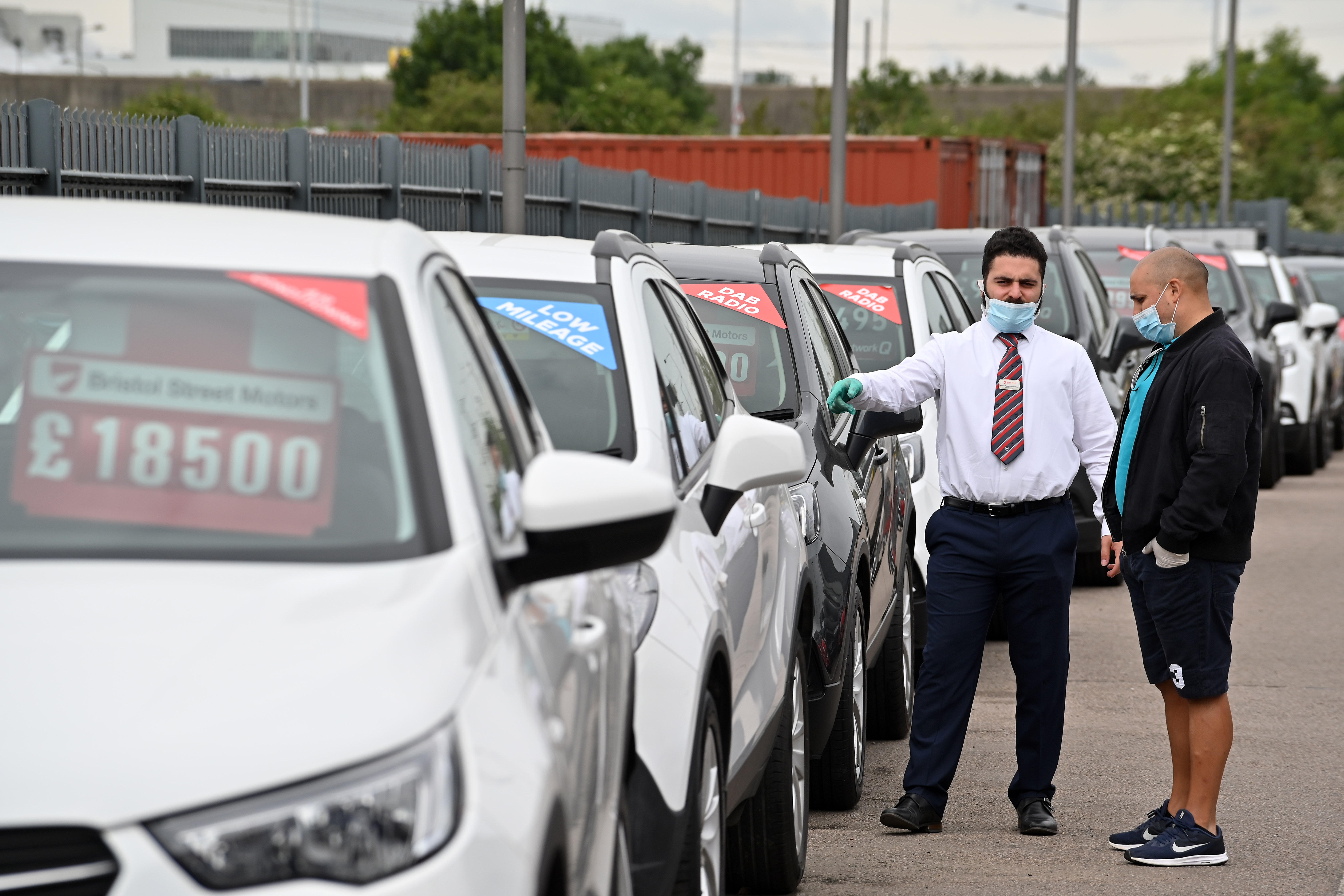 A car salesman (L) wearing PPE (personal protective equipment) including a face mask as a precautionary measure against COVID-19, shows customers vechiles parked on the forecourt of a recently re-opened Vauxhall car dealership in north London on June 4, 2020, as lockdown restrictions are eased during the noel coronavirus COVID-19 pandemic. - Car showrooms in England reopened this week as the UK government eased COVID-19 lockdown measures that have slammed the brakes on the industry. (Photo by JUSTIN TALLIS / AFP) (Photo by JUSTIN TALLIS/AFP via Getty Images)