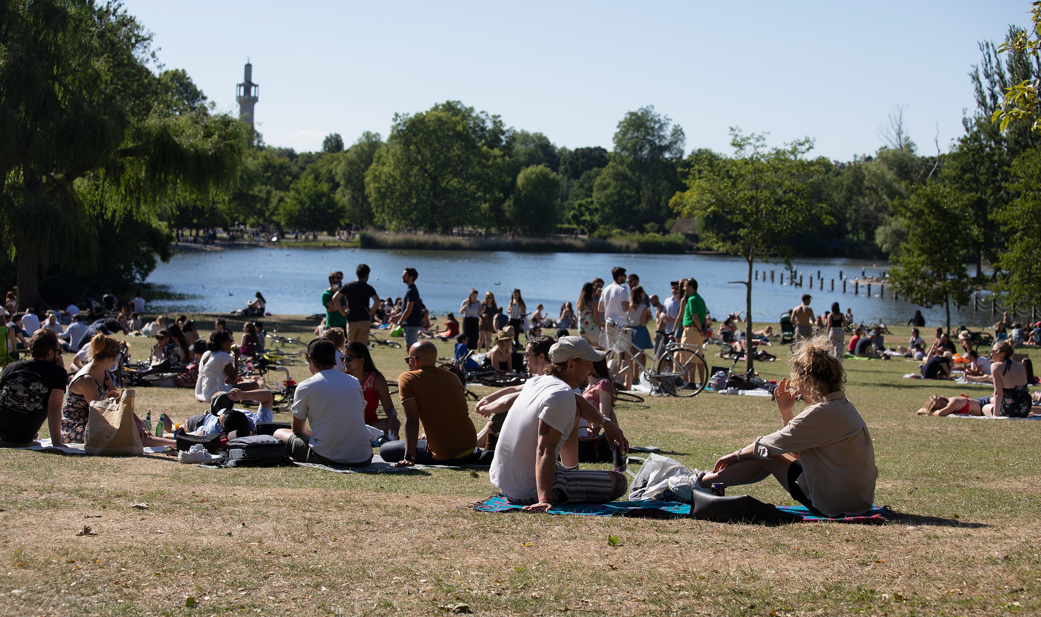 LONDON, ENGLAND - JUNE 01: Groups of people sunbathing by the lake in Regent's Park during warm sunny weather on June 01, 2020 in London, UK. The British government further relaxed Covid-19 quarantine measures in England this week, allowing groups of six people from different households to meet in parks and gardens, subject to social distancing rules. Many schools also reopened and vulnerable people who are shielding in their homes are allowed to go outside again. (Photo by Jo Hale/Getty Images)