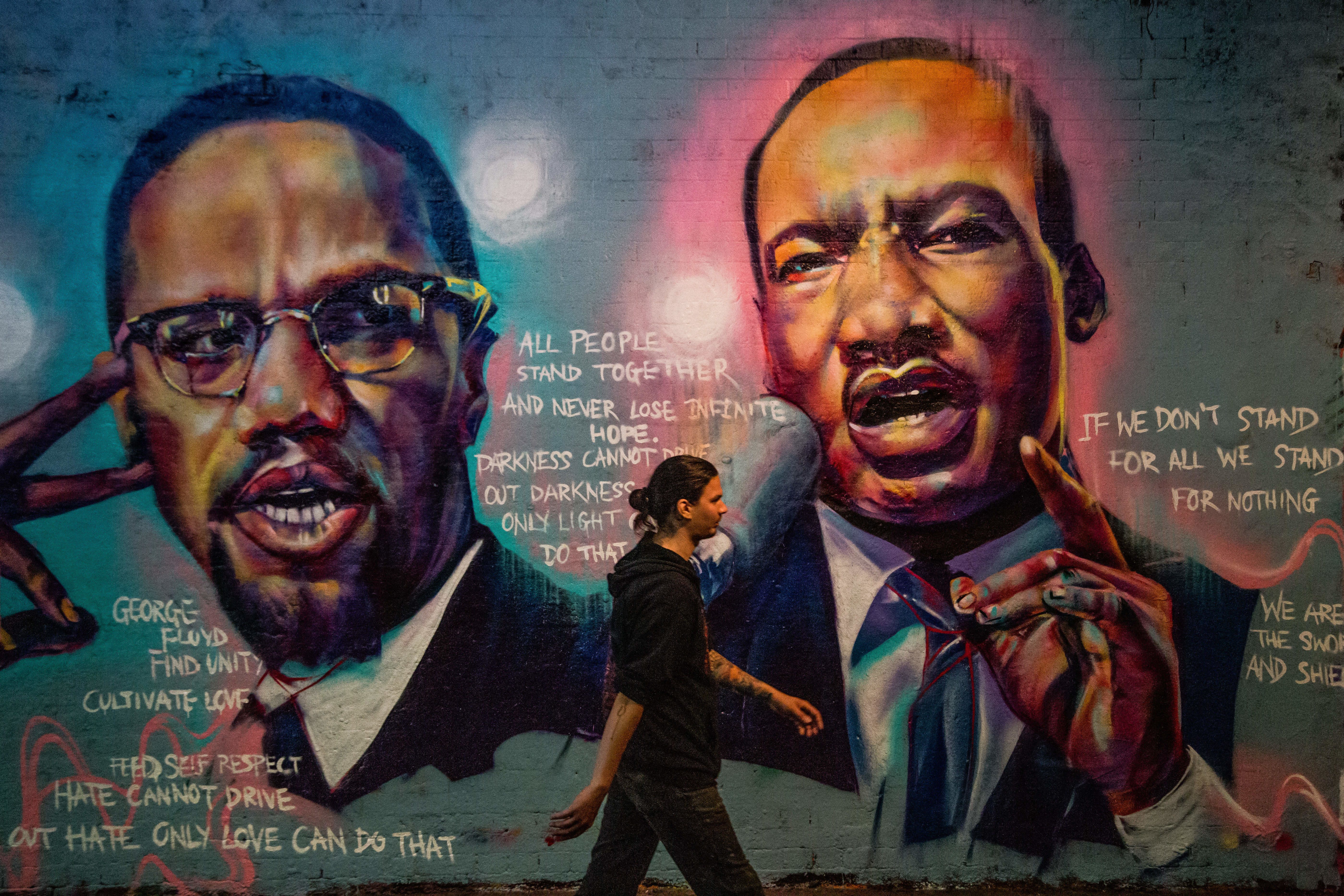 A man walks past a mural of Malcom X and Martin Luther King paying tribute to George Floyd, a Black man who died in police custody in the U.S. Artists have been painting murals and sharing messages in London. (Photo by Thabo Jaiyesimi / SOPA Images/Sipa USA)