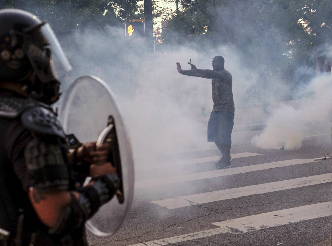 A protester tries to talk the police back amid tear gas in downtown Atlanta, Sunday, May 31, 2020. Protests continue across the country over the death of George Floyd, a black man who died after being restrained by Minneapolis police officers on May 25. (Ben Gray/Atlanta Journal-Constitution via AP)