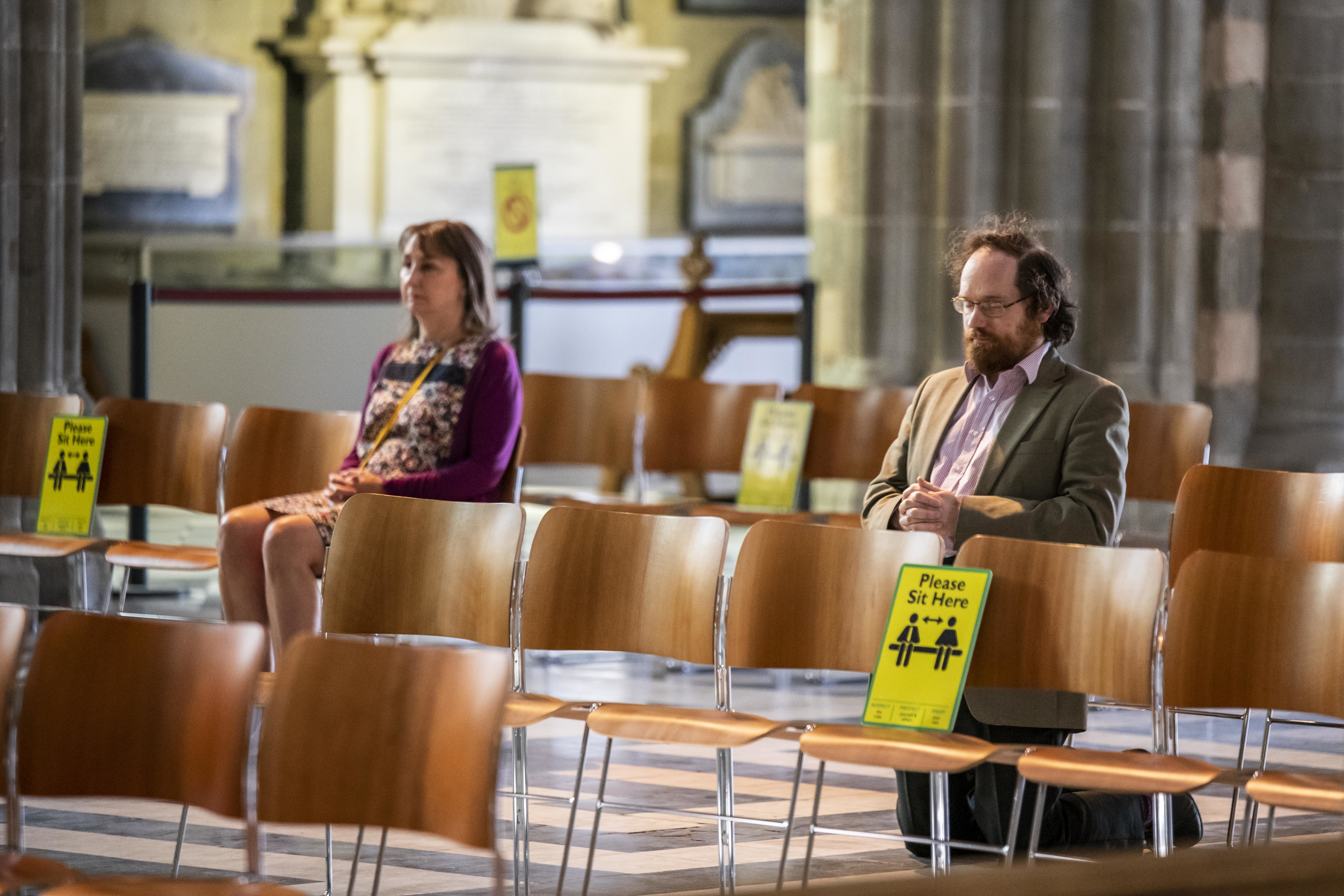 People sit in prayer in the nave of Worcester Cathedral in Worcester, Worcestershire, as it opens for the first time since the UK entered lockdown to reduce the spread of coronavirus.