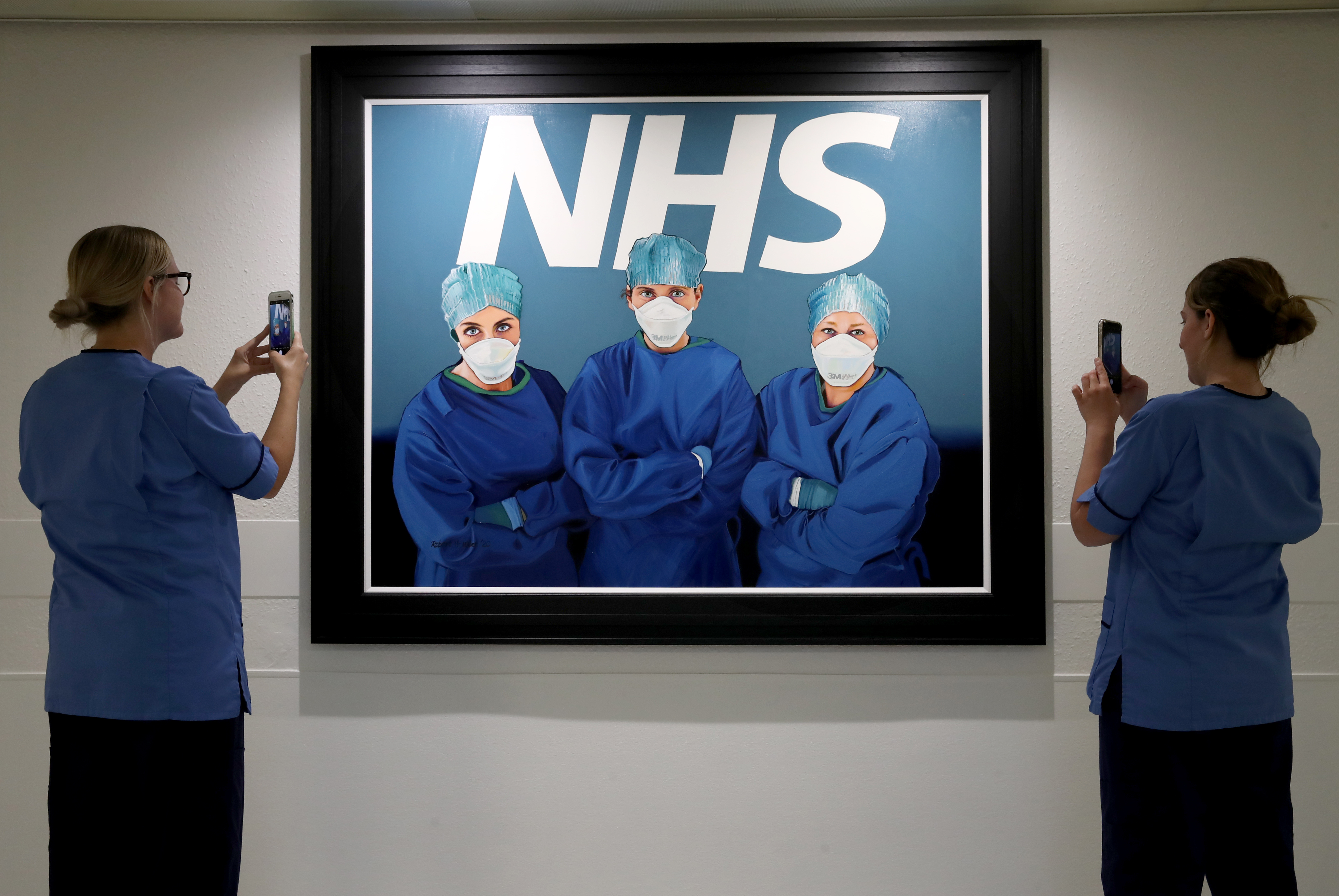 Nurses view a painting by Glasgow artist Robert Miller of three NHS colleagues on the frontline in the fight against Covid-19. It hangs just outside the Intensive Care Unit of Glasgow Royal Infirmary. (Photo by Andrew Milligan/PA Images via Getty Images)