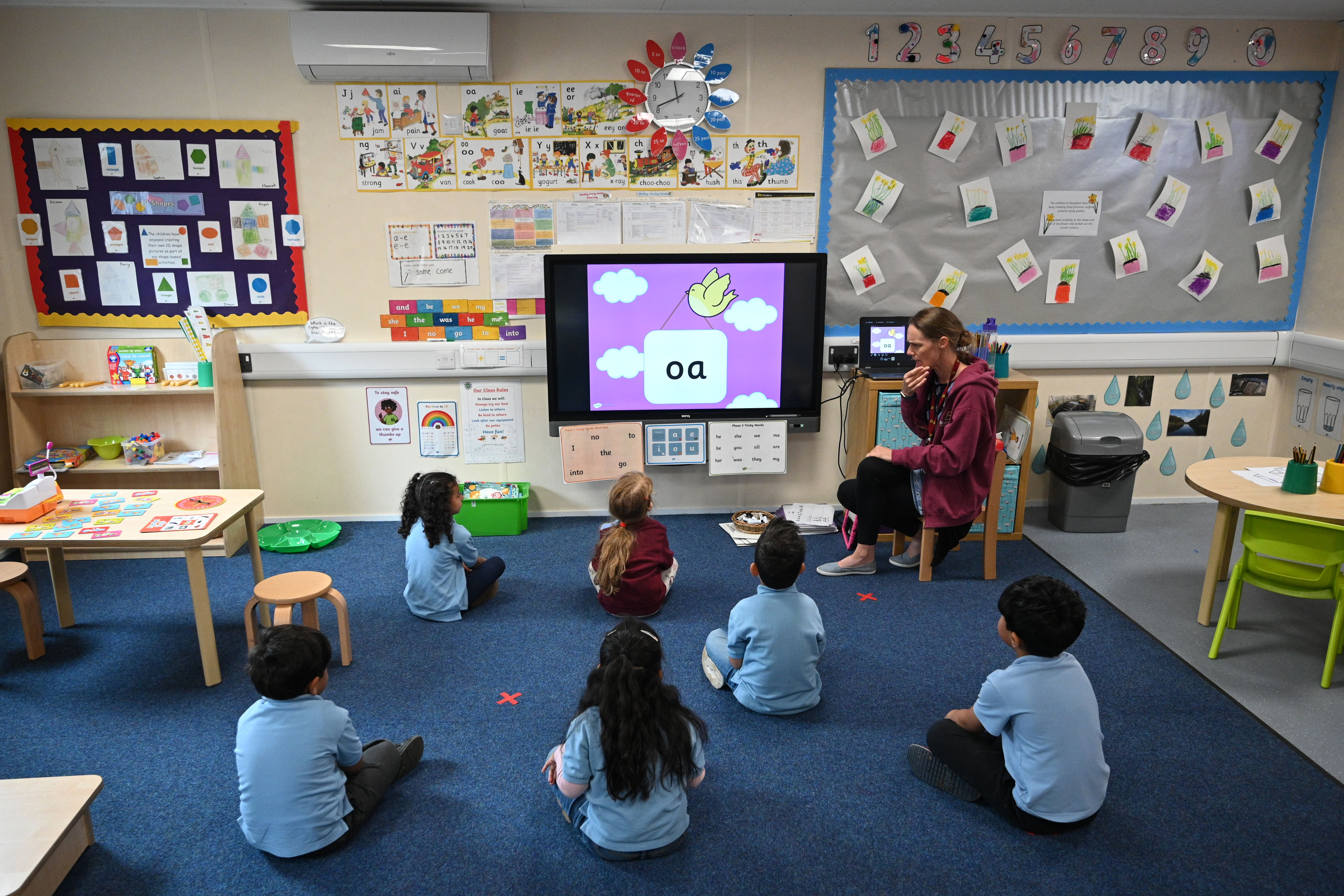In a reception classroom, children sit apart from each other on a carpet where crosses have been marked out for them to sit on, in a teaching environment safe from Coronavirus for pupils and teachers at Brambles Primary Academy in Huddersfield, northern England on June 4, 2020, as the Government's recommencing of education for Reception and Years 1 and 6 classes gets underway. - Primary schools reopened the week commencing June 1, welcoming back children in Reception, year 1 and year 6 age groups, alongside priority groups. (Photo by Oli SCARFF / AFP) (Photo by OLI SCARFF/AFP via Getty Images)