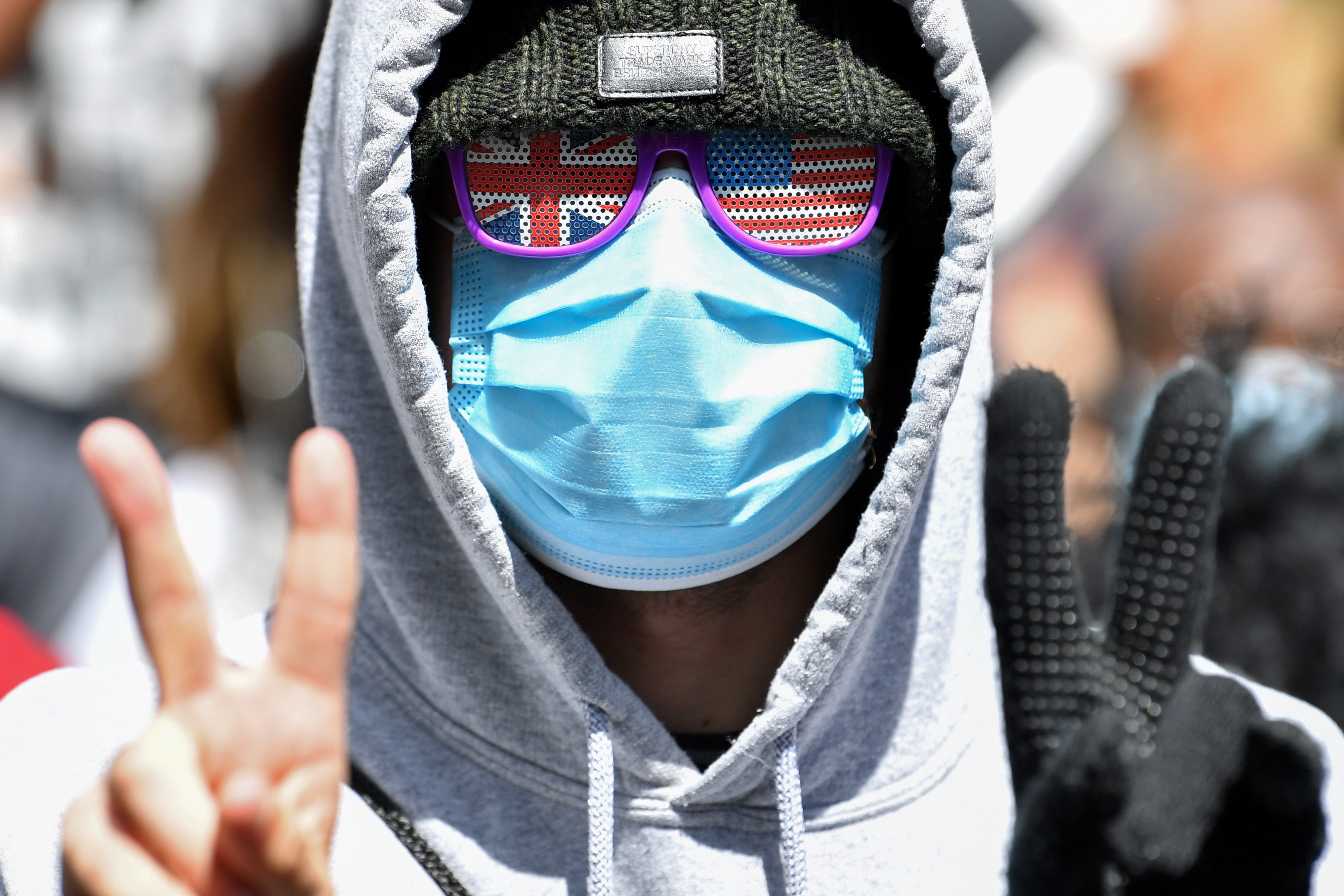 """A demonstrator, wearing PPE (personal protective equipment), including a face mask as a precautionary measure against COVID-19, and sunglasses themed on the Union and US flags, gestures during a protest march in Manchester, northern England, on June 6, 2020, to show solidarity with the Black Lives Matter movement in the wake of the killing of George Floyd, an unarmed black man who died after a police officer knelt on his neck in Minneapolis. - The United States braced Friday for massive weekend protests against racism and police brutality, as outrage soared over the latest law enforcement abuses against demonstrators that were caught on camera. With protests over last week's police killing of George Floyd, an unarmed black man, surging into a second weekend, President Donald Trump sparked fresh controversy by saying it was a """"great day"""" for Floyd. (Photo by Paul ELLIS / AFP) (Photo by PAUL ELLIS/AFP via Getty Images)"""