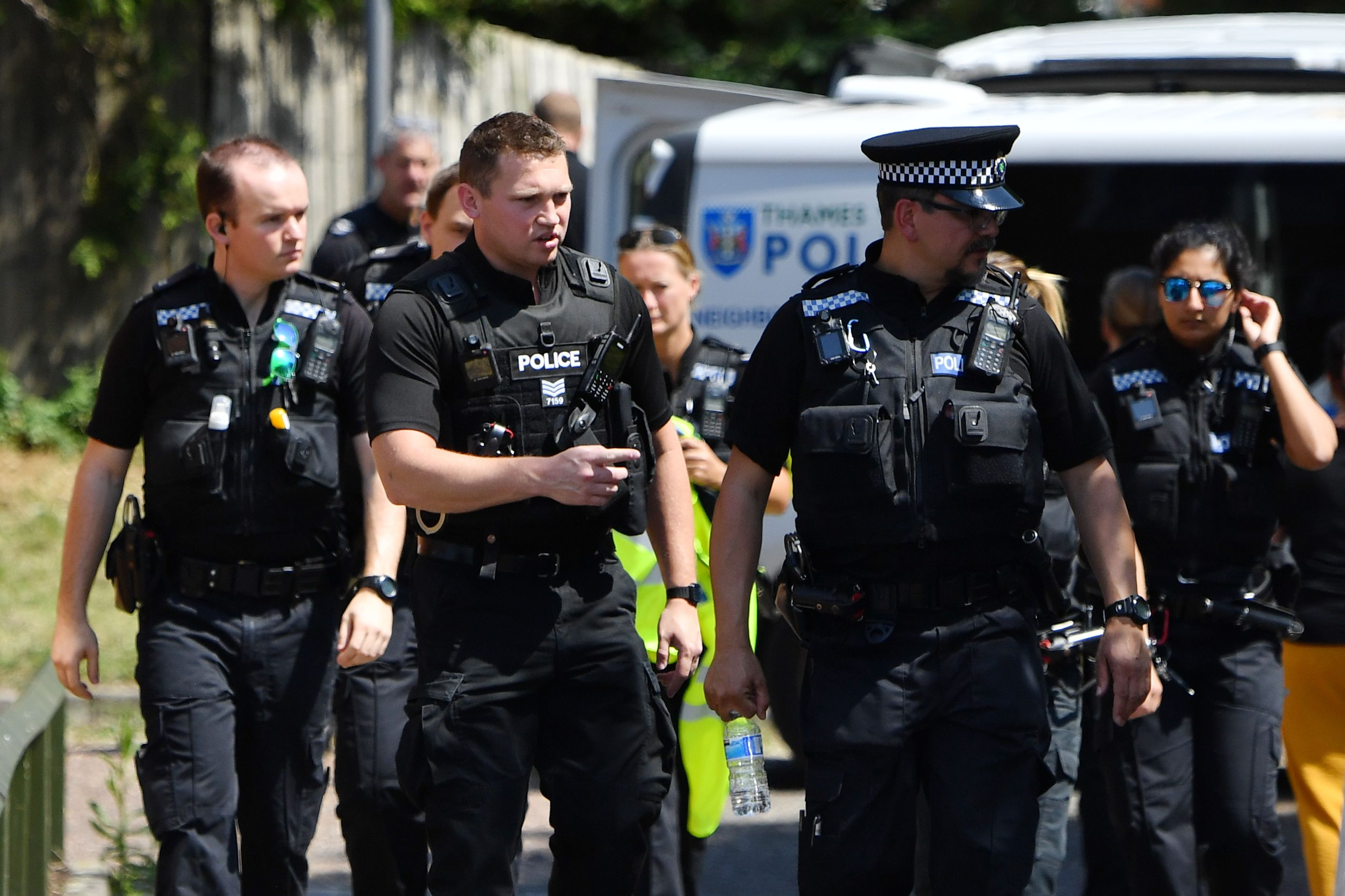 Police officers congregate outside a cordoned off block of flats where the suspect of a multiple stabbing incident lived in Reading, west of London, on June 23, 2020. - British counter-terrorism police have been given until June 27 to question a suspect widely identified as Libyan Khairi Saadallah in an attack which saw three people stabbed to death in a park, officers said. (Photo by Ben STANSALL / AFP) (Photo by BEN STANSALL/AFP via Getty Images)