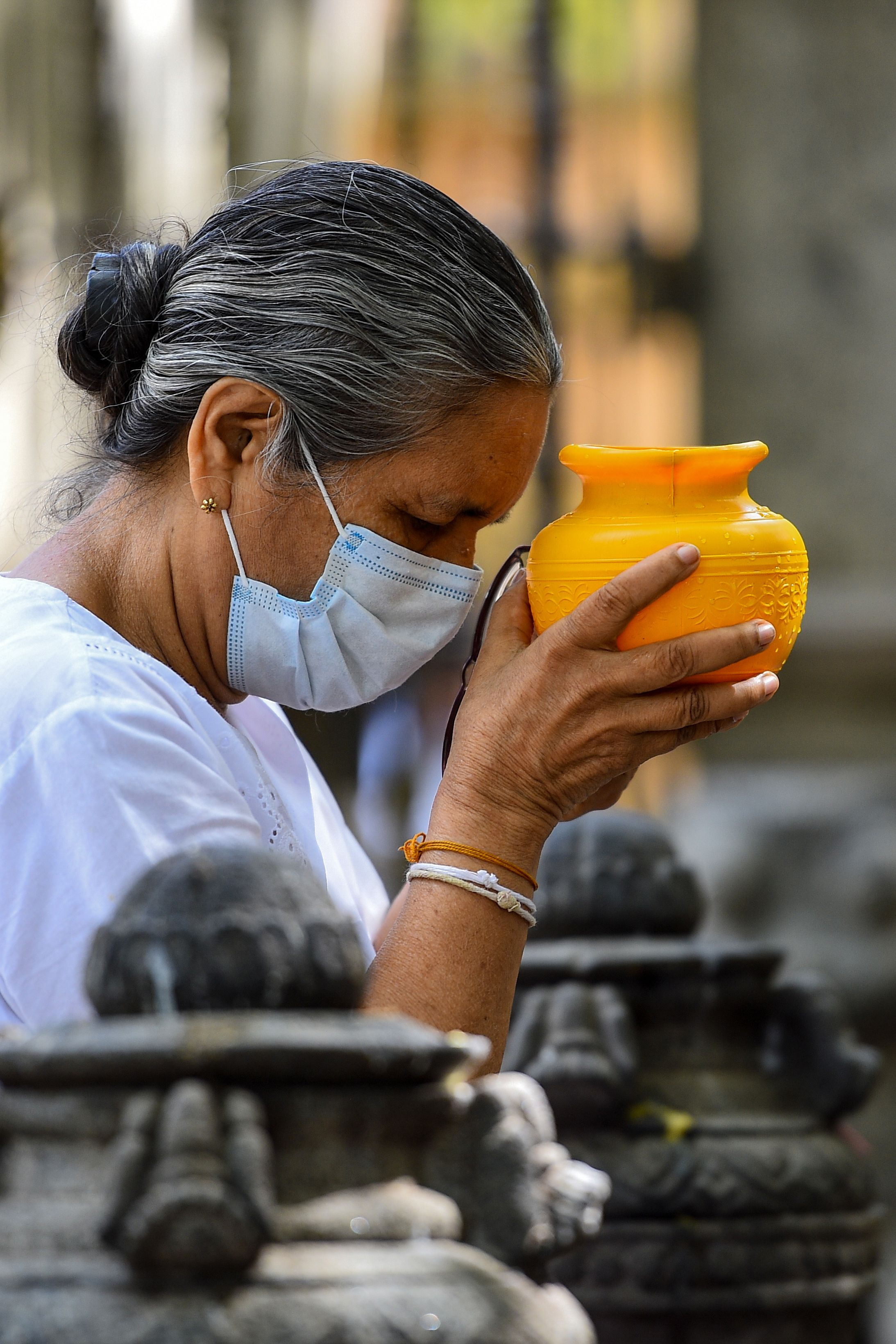 A Buddhist devotee holds a pot of water while offering prayers at the Kelaniya temple during the Poson Poya (full moon) religious festival marking the arrival of Buddhism in the island, on the outskirts of Colombo on June 5, 2020. - Sri Lanka on June 5 marked a key Buddhist festival with a nation-wide 24-hour curfew as devotees were urged to remain indoors to help prevent the spread of the coronavirus. (Photo by ISHARA S. KODIKARA / AFP) (Photo by ISHARA S. KODIKARA/AFP via Getty Images)