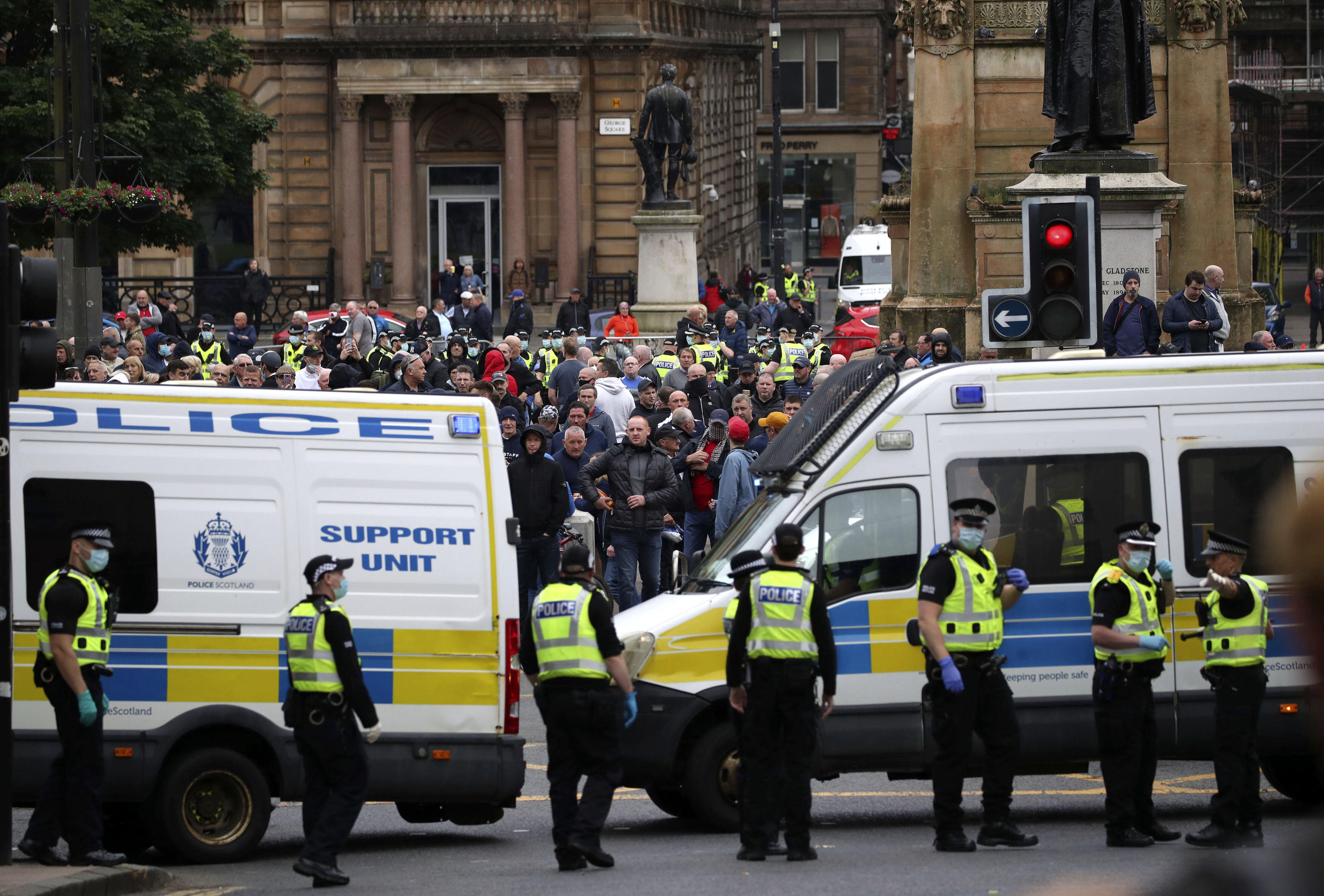 Loyalist Defence League members gather in George Square in Glasgow, Sunday June 14, 2020, during a protest between people calling for the removal of a statue Robert Peel and counter protesters. (Jane Barlow/PA via AP)