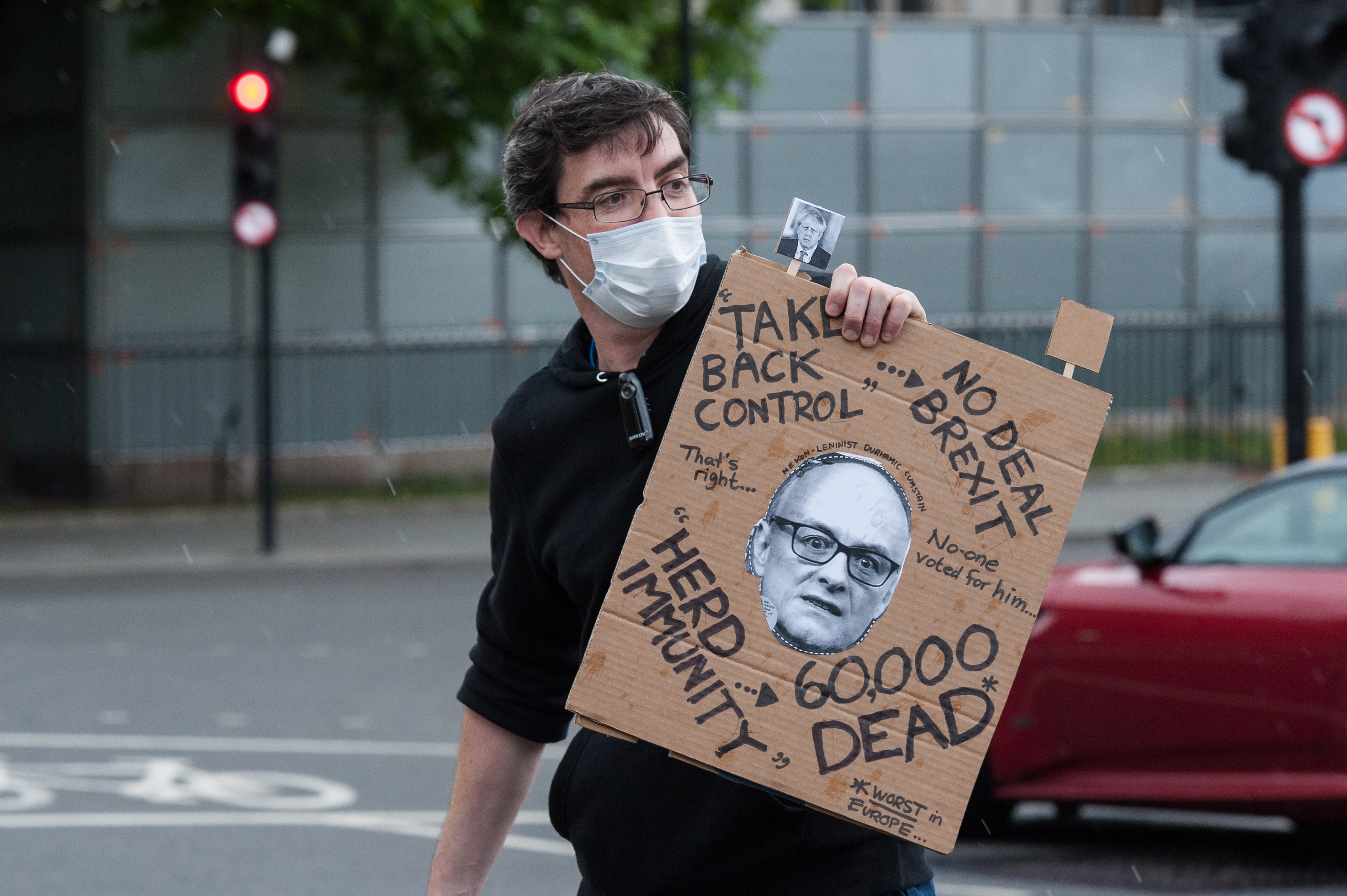 A protestor holds a placard depicting Dominic Cummings, Special Political Advisor for the Prime Minister Boris Johnson, as pro-EU supporters demonstrate outside Houses of Parliament against no-deal Brexit and call for an extension of the transition period on 17 June, 2020 in London, England. The EU and the UK are negotiating the post-Brexit relationship as Britain's transition period ends in December. (Photo by WIktor Szymanowicz/NurPhoto via Getty Images)