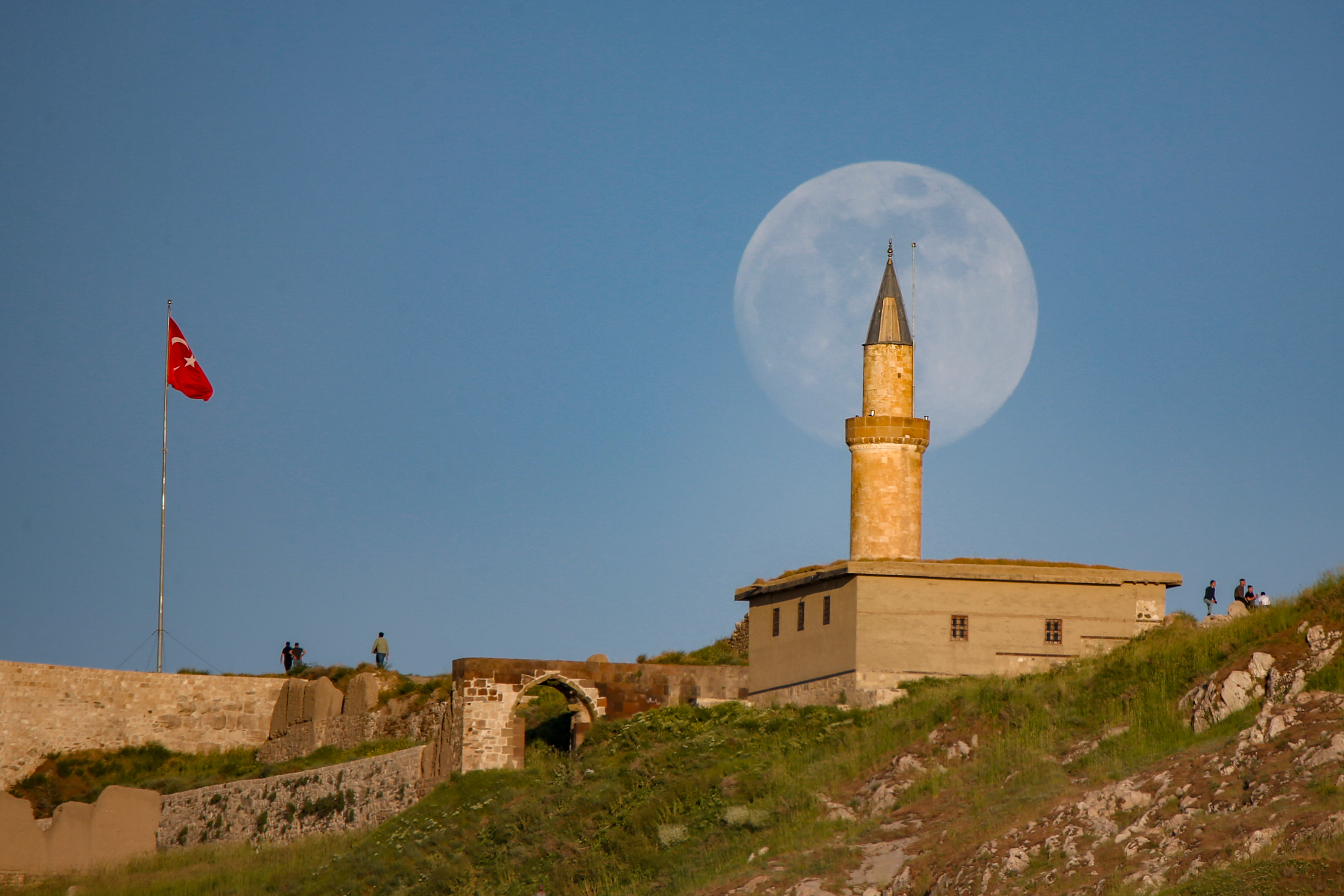"""VAN, TURKEY - JUNE 04: Full moon rises over Suleyman Han Mosque on the summit of Van Castle on June 04, 2020, in Van province, Turkey.  People allowed to visit historical places with the """"new normal"""" process as authorities took a set of new decisions to ease restrictions related to the novel coronavirus (COVID-19) whilst the country made advances in its fight against the pandemic. (Photo by Ozkan Bilgin/Anadolu Agency via Getty Images)"""