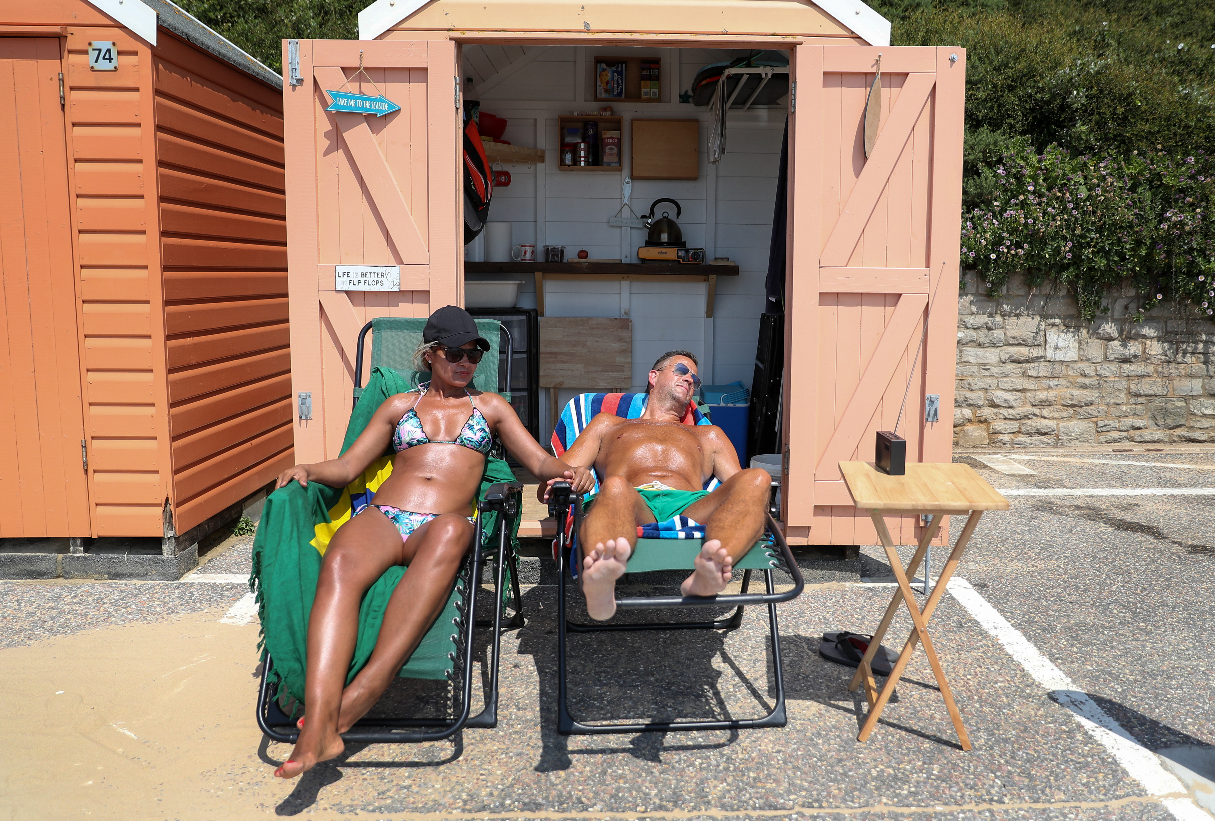 PERMISSION GIVEN A couple relax outside their beach hut on the beach in Bournemouth, Dorset, as Britain is braced for a June heatwave with temperatures set to climb into the mid-30s this week. (Photo by Andrew Matthews/PA Images via Getty Images)