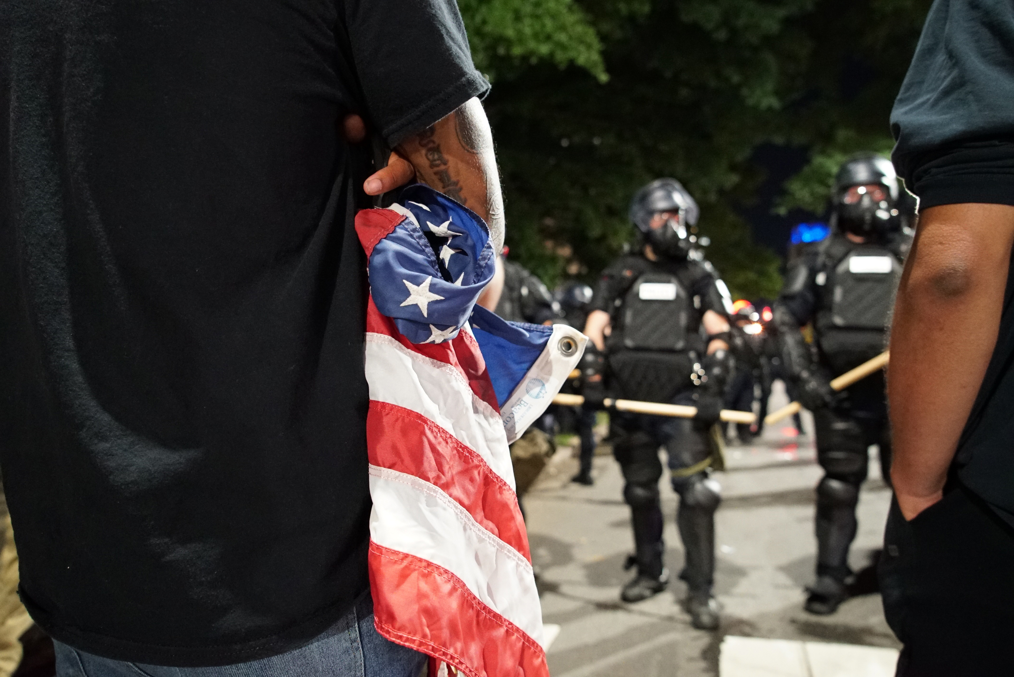 A protester holds a tattered American flag as police stand guard over the old state capitol in in Raleigh, N.C., on Sunday, May 31, 2020. It was the second day of protests in the North Carolina capital following the death of Minnesotan George Floyd while in police custody. (AP Photo/Allen G. Breed)
