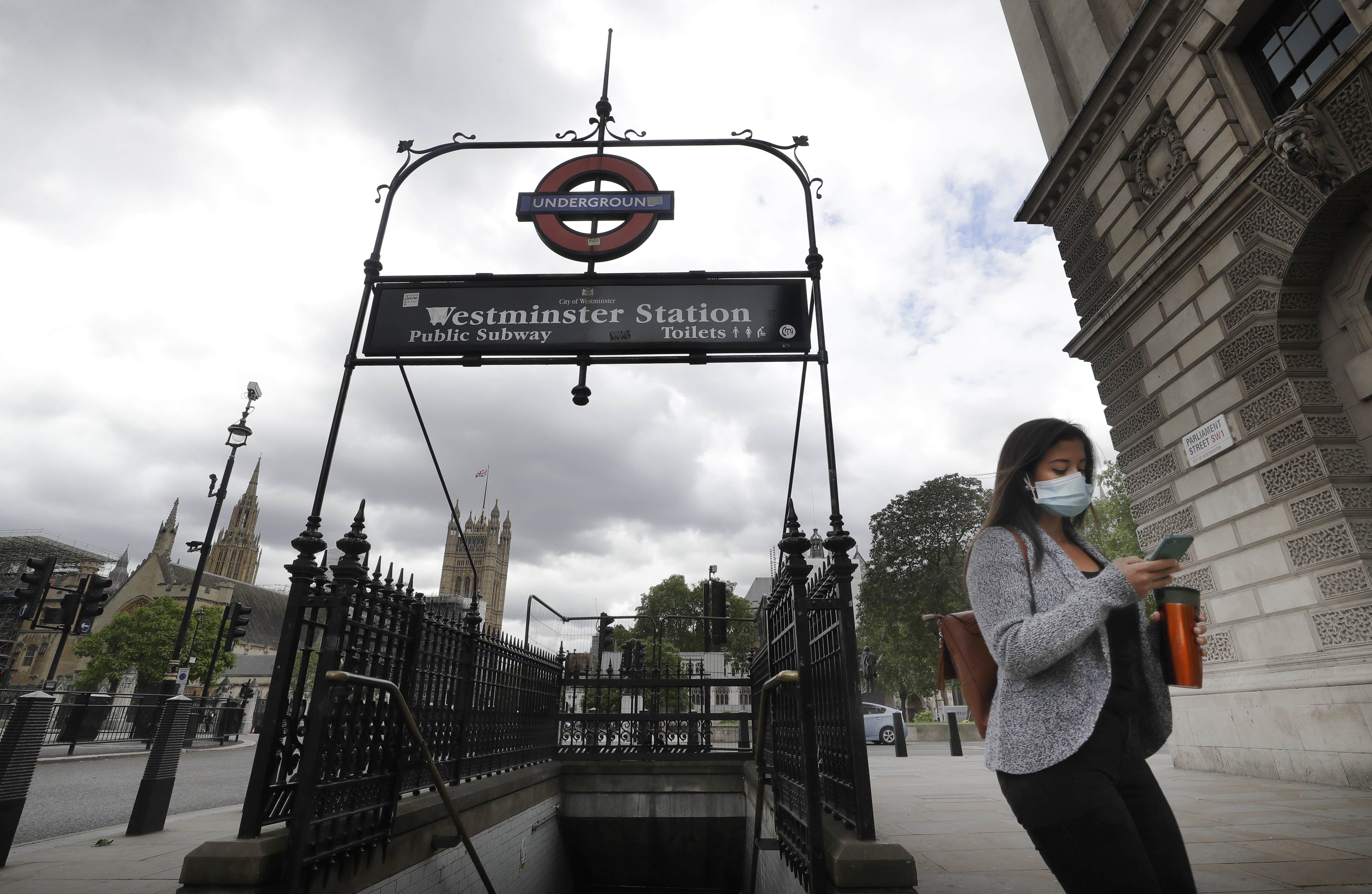 A woman wears a mask as she passes Westminster Station in London, Friday, June 5, 2020.  It will become compulsory to wear face coverings whilst using public transport in England from Monday June 15. (AP Photo/Kirsty Wigglesworth)