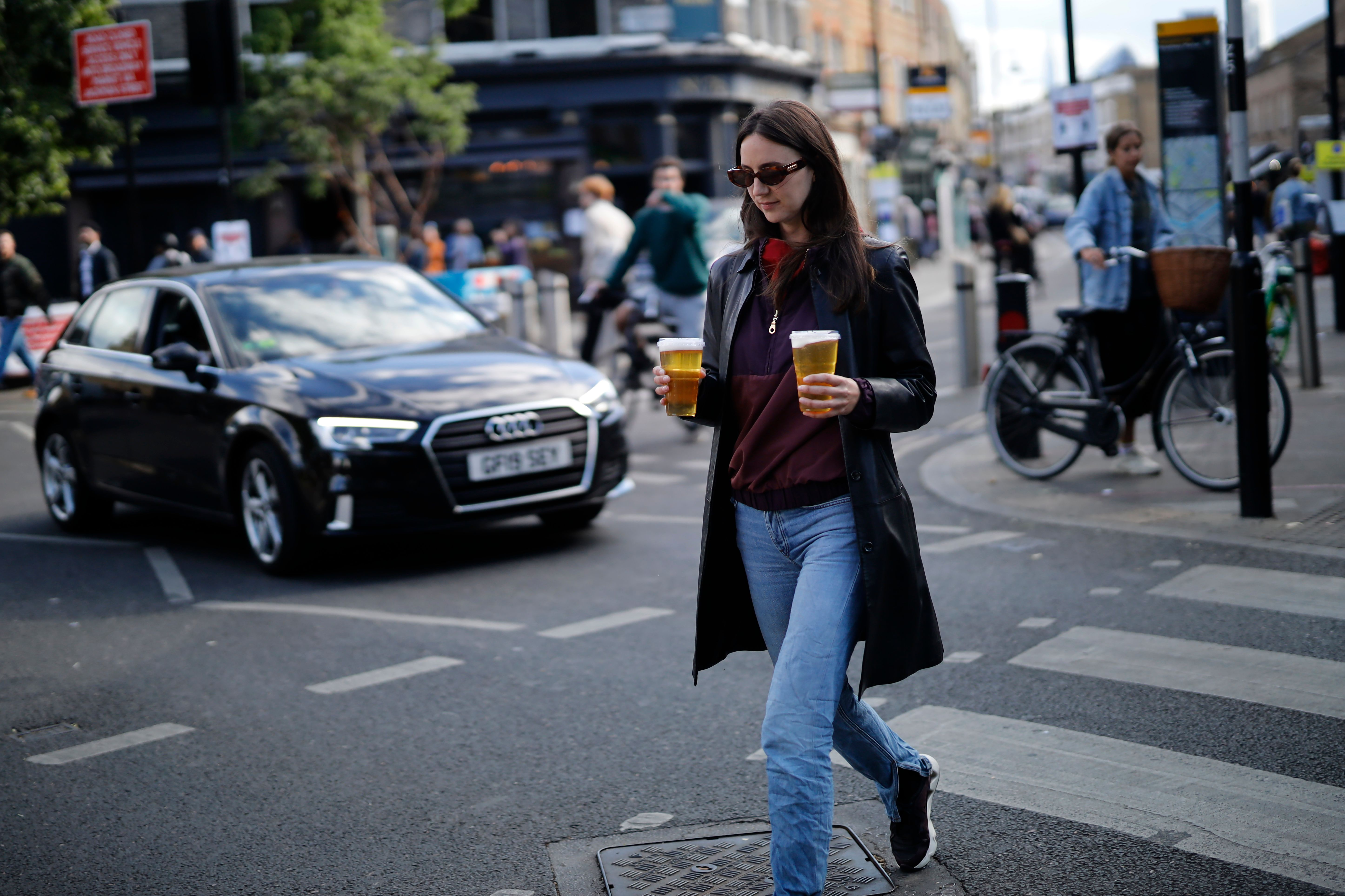 A woman carries takeaway draught beer in plastic cups from a pub in Broadway Market, London on June  5, 2020, as lockdown measures are eased during the novel coronavirus COVID-19 pandemic. (Photo by Tolga Akmen / AFP) (Photo by TOLGA AKMEN/AFP via Getty Images)