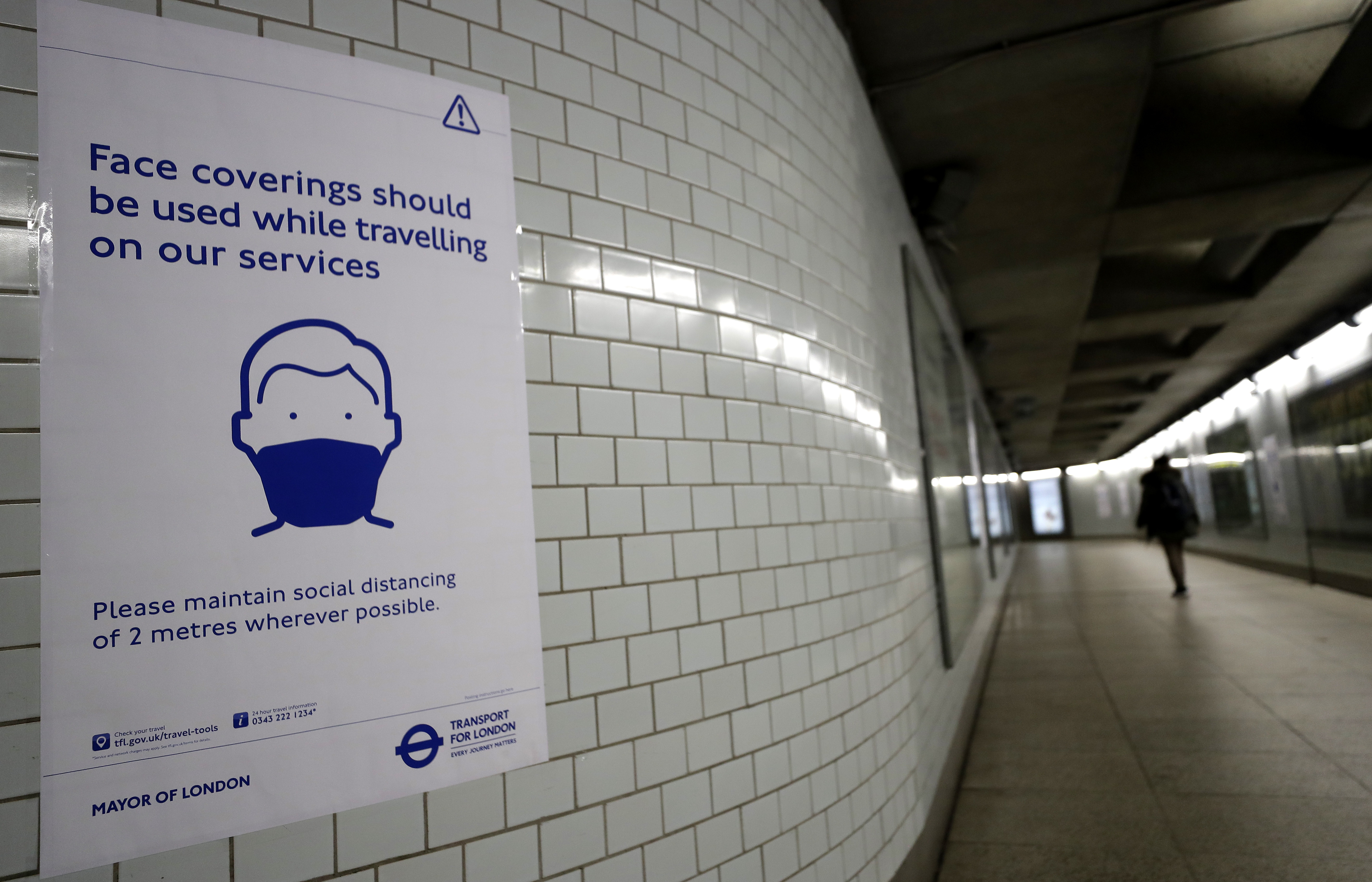 A sign advises travellers to wear face coverings at Westminster Station in London, Friday, June 5, 2020.  It will become compulsory to wear face coverings whilst using public transport in England from Monday June 15. (AP Photo/Kirsty Wigglesworth)