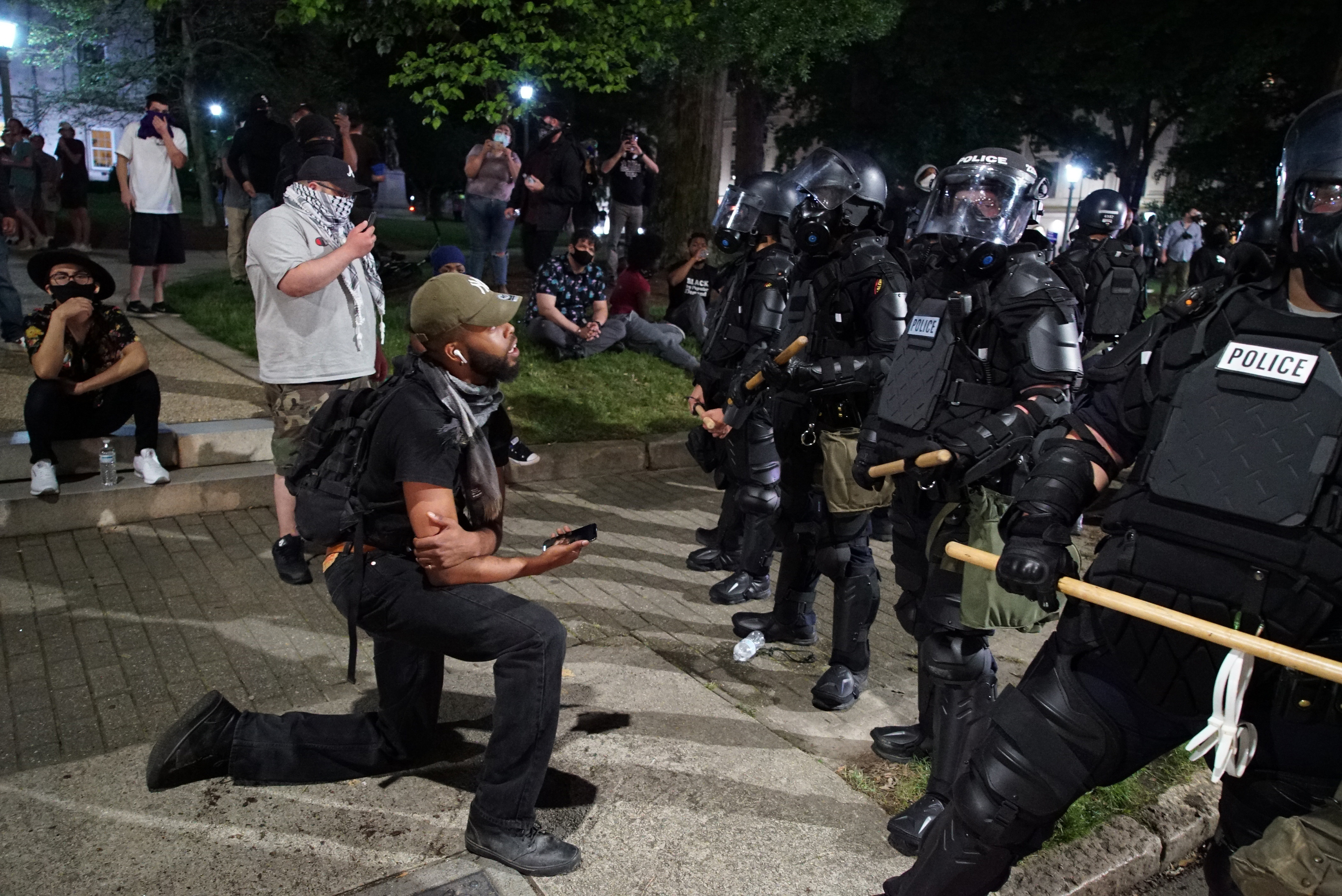A protester takes a knee as he tries to talk with police guarding the old state capitol in Raleigh, N.C., on Sunday, May 31, 2020. It was the second day of protests in the North Carolina capital following the death of Minnesotan George Floyd while in police custody. (AP Photo/Allen G. Breed)