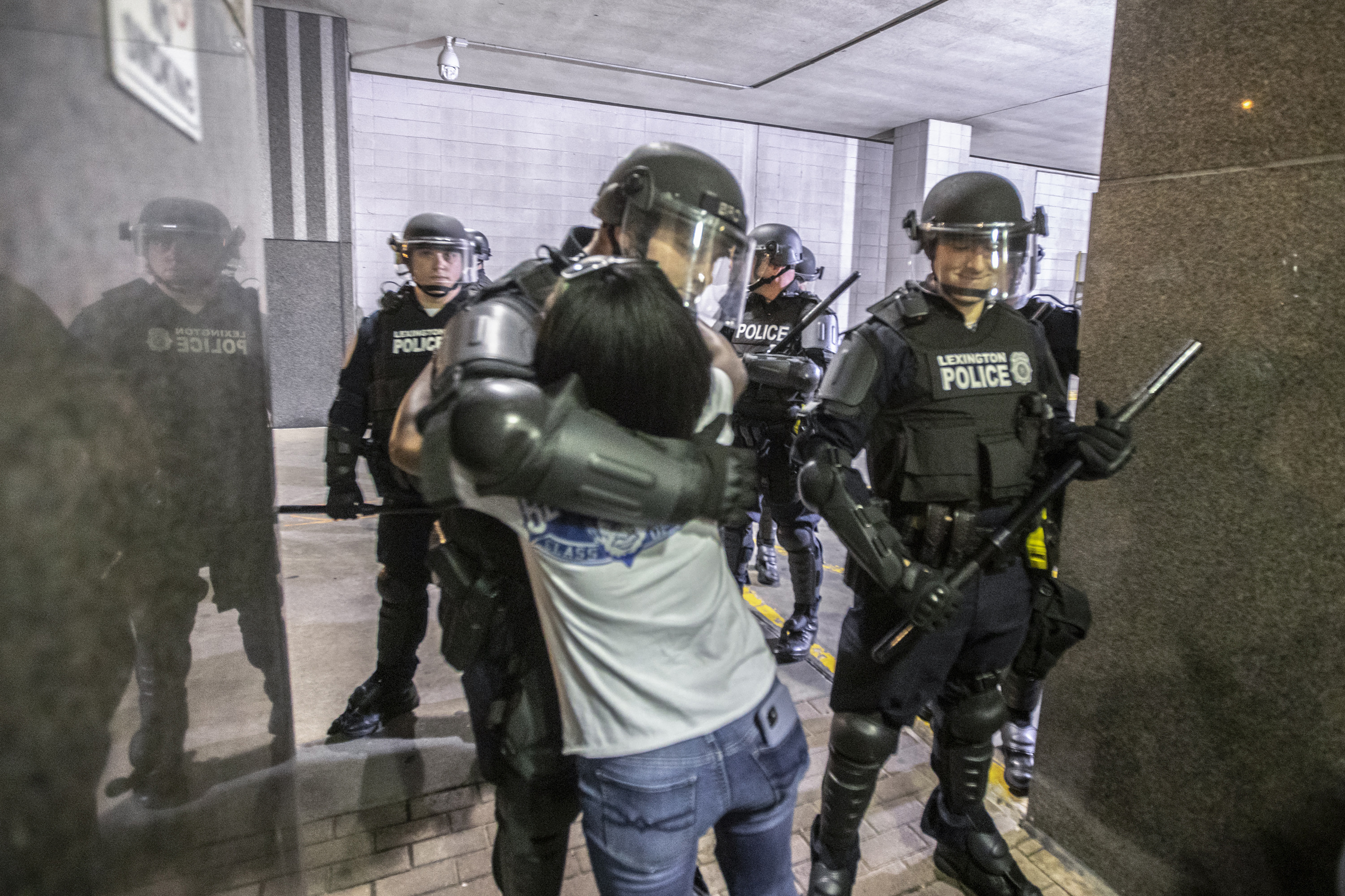 """A protester hugs a police officer who kneeled after protesters attending a rally against the deaths of George Floyd and Breonna Taylor chanted """"Kneel with us! Kneel with us!"""" in Lexington, Ky., on Sunday, May 31, 2020. (Ryan C. Hermens/Lexington Herald-Leader via AP)"""