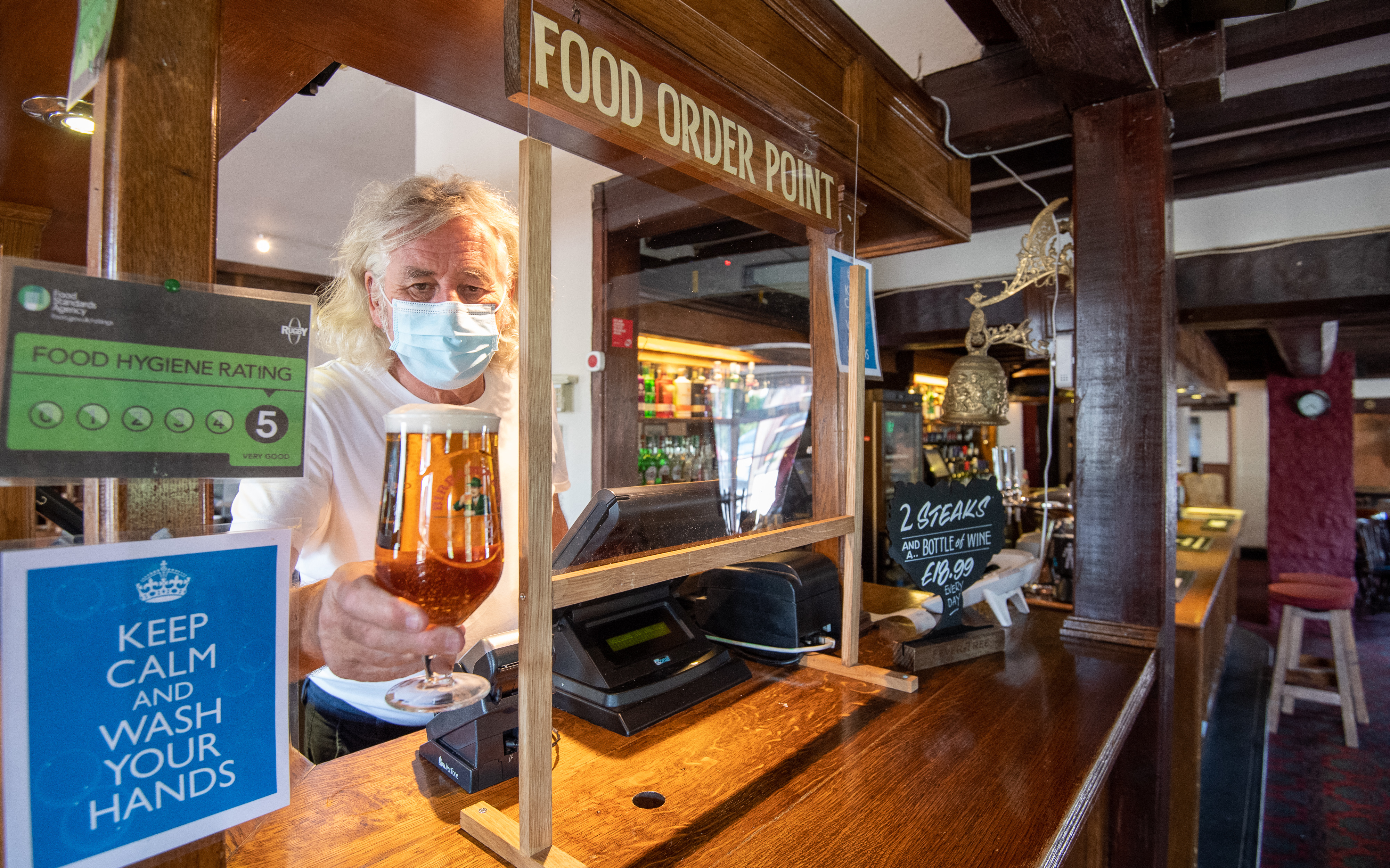 """Phil Weaver, owner of The Old Smithy pub in Church Lawford, Warwickshire holds a pint of beer from behind a protective screen, as pub and hospitality bosses have cheered the Government's proposals to allow customers through their doors again on July 4 as """"a welcome relief""""."""