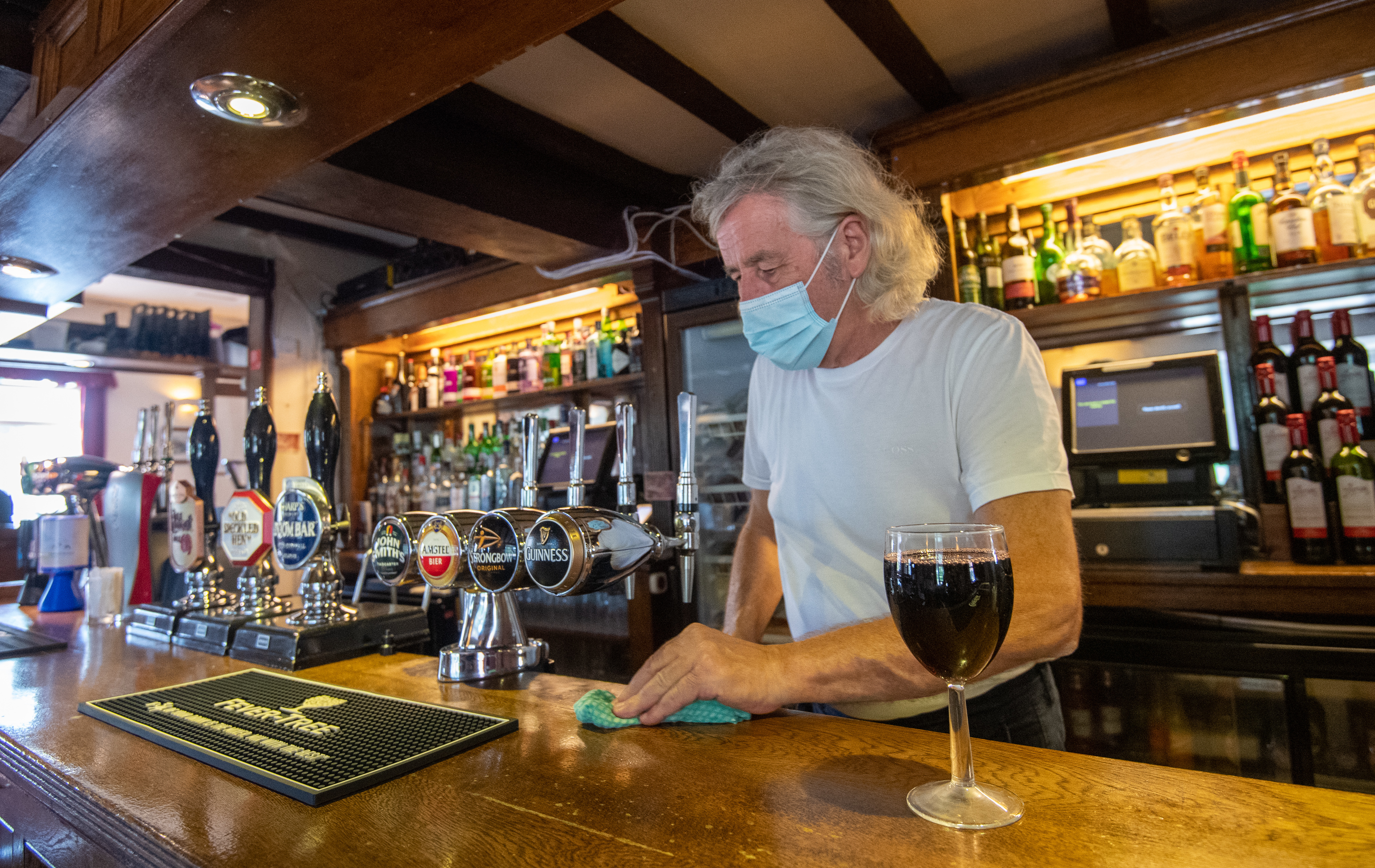 """Phil Weaver, owner of The Old Smithy in Church Lawford, Warwickshire wipes down the bar as pub and hospitality bosses have cheered the Government's proposals to allow customers through their doors again on July 4 as """"a welcome relief""""."""