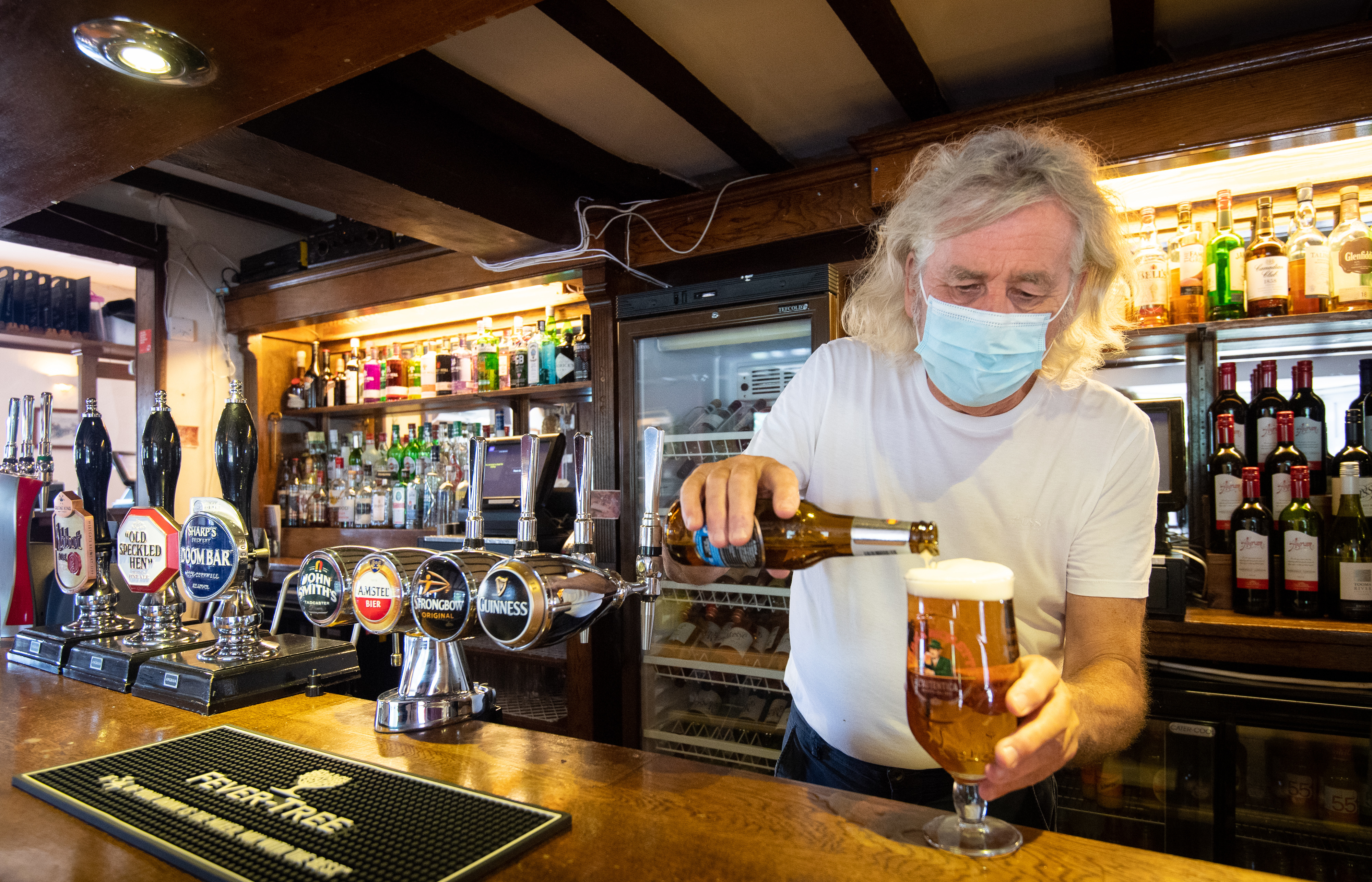 """Phil Weaver, owner of The Old Smith in Church Lawford, Warwickshire pours a drink as pub and hospitality bosses have cheered the Government's proposals to allow customers through their doors again on July 4 as """"a welcome relief""""."""