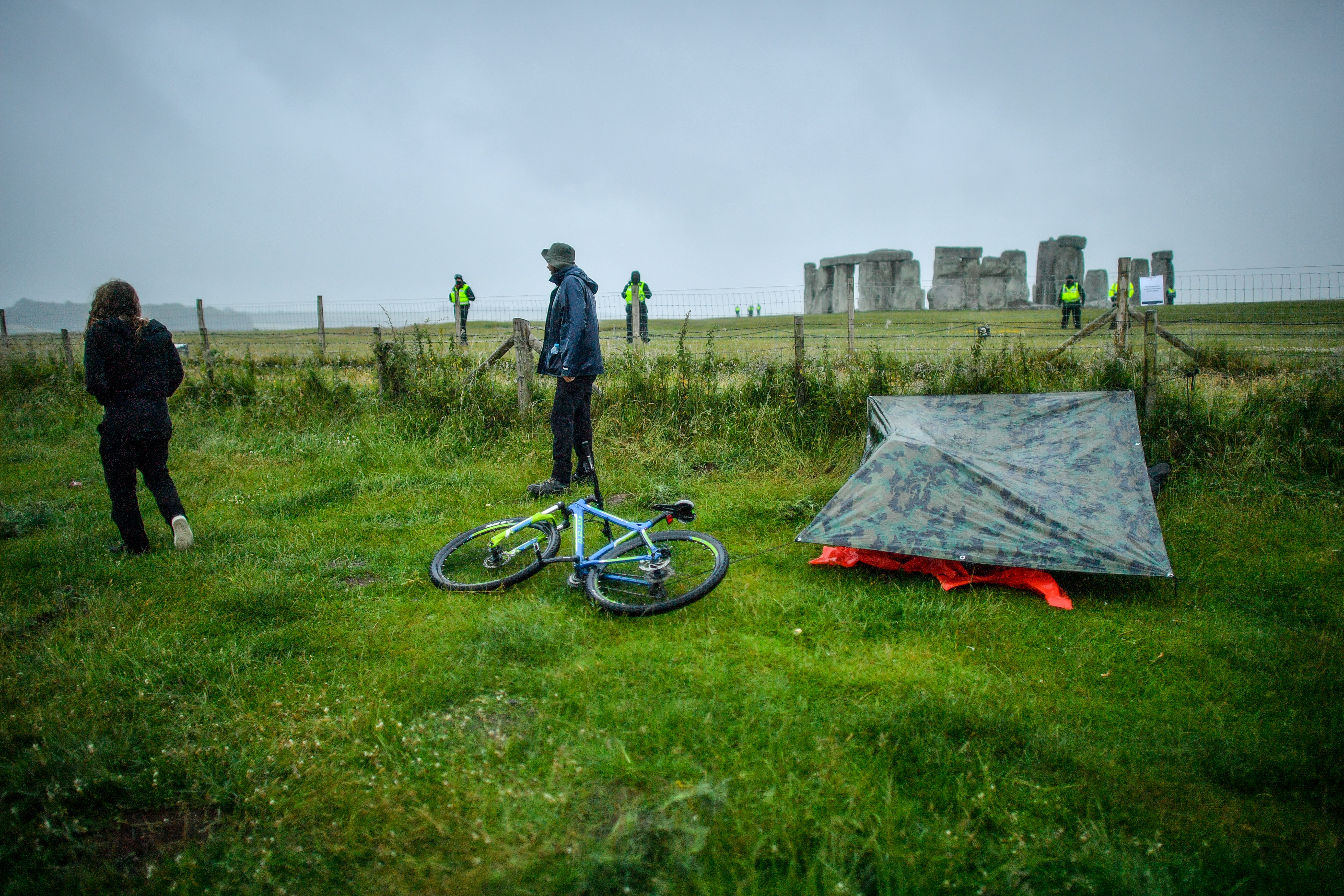 People camp under a bivouac during showers next to a closed Stonehenge as people gather to celebrate the dawn of the longest day in the UK.