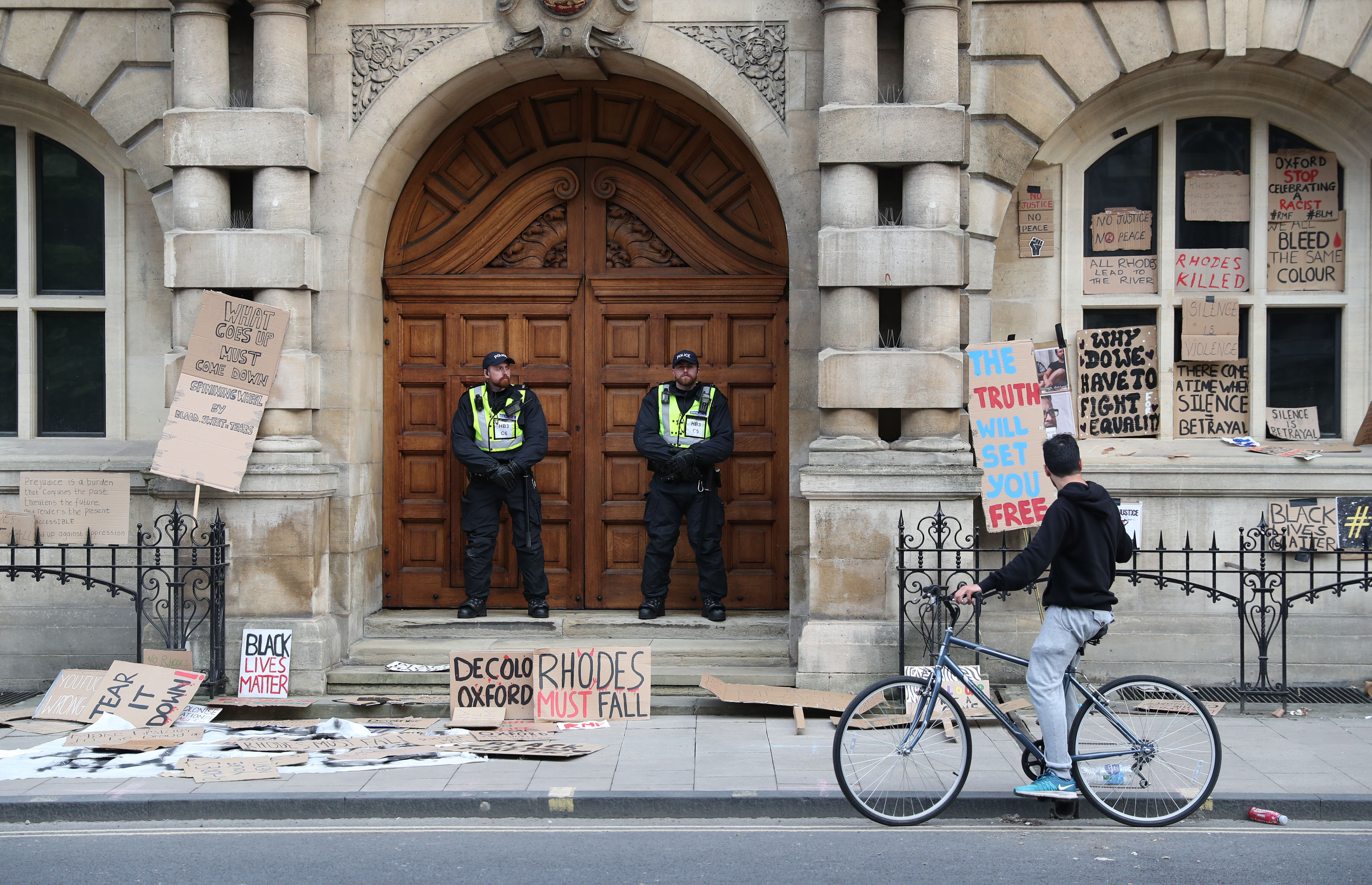 Police during a protest calling for the removal of the statue of 19th century imperialist, politician Cecil Rhodes from an Oxford college which has reignited amid anti-racism demonstrations.