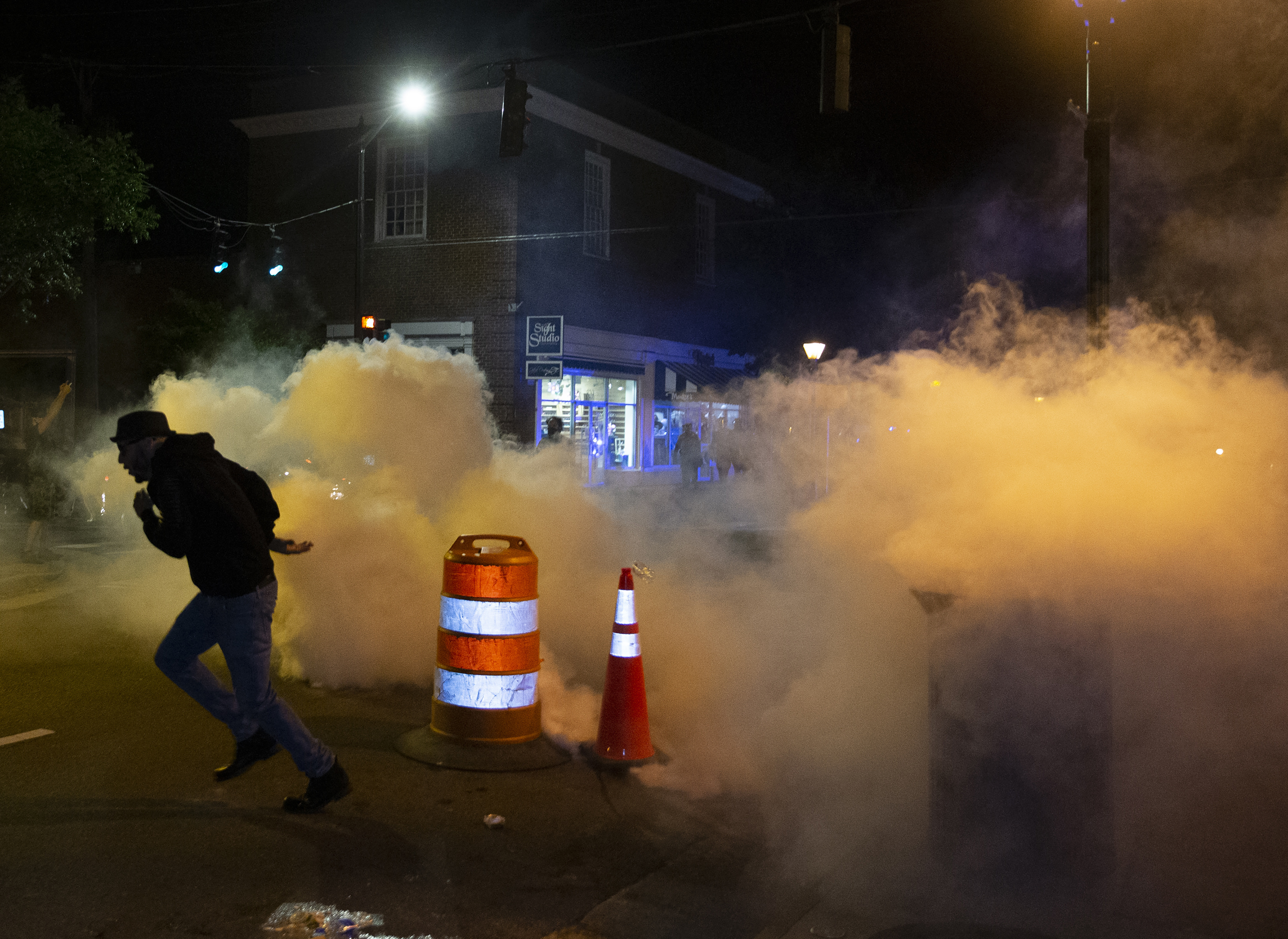 A protester runs after placing a construction barrel on top of a gas grenade in downtown Fredericksburg, Va. on Sunday, May 31, 2020. (Mike Morones/The Free Lance-Star via AP)
