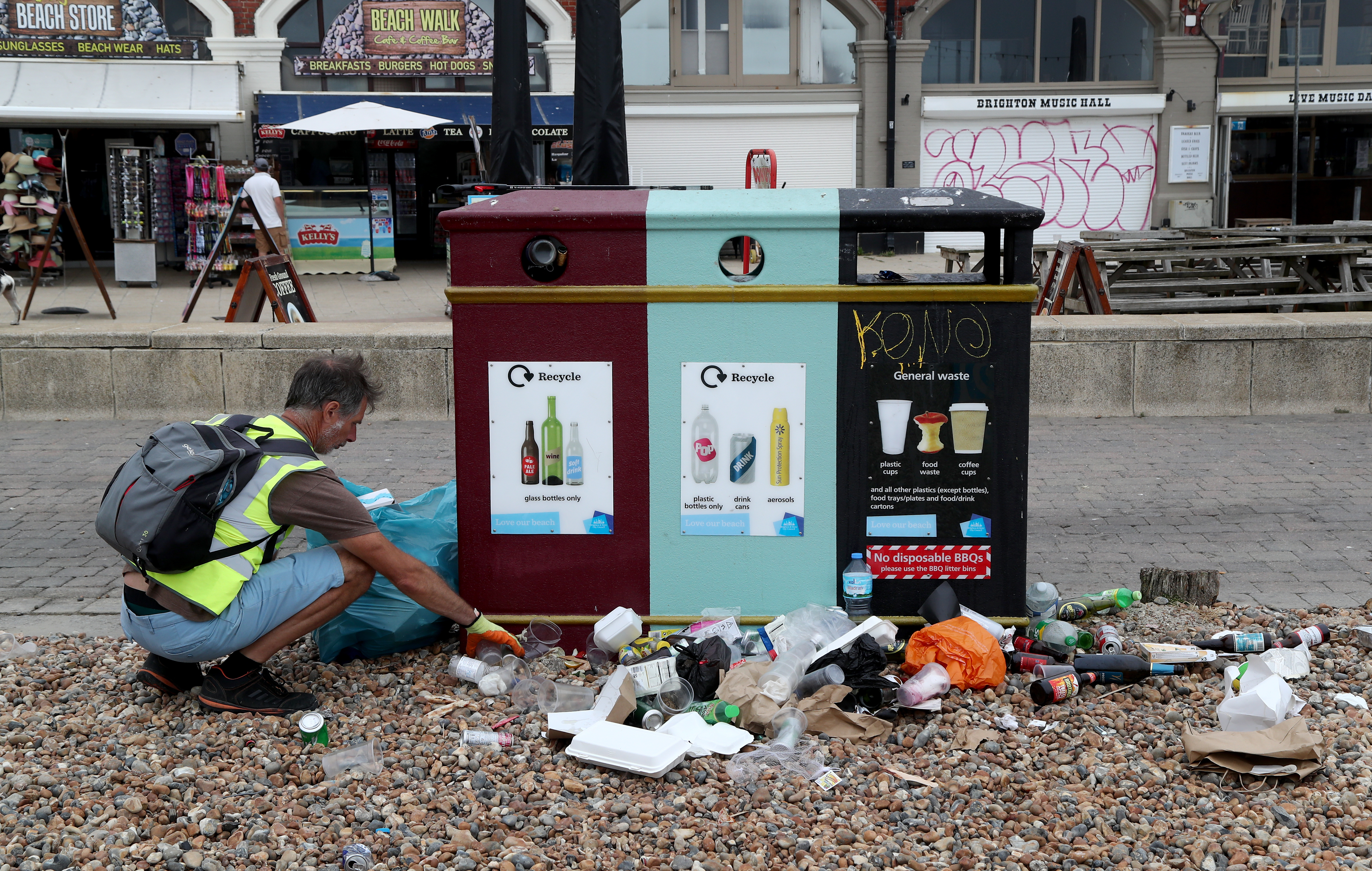 A man clears rubbish left by beachgoers in Brighton as thunderstorms and torrential rain are forecast to sweep across the UK, bringing an end to a week of blazing sunshine and scorching temperatures.