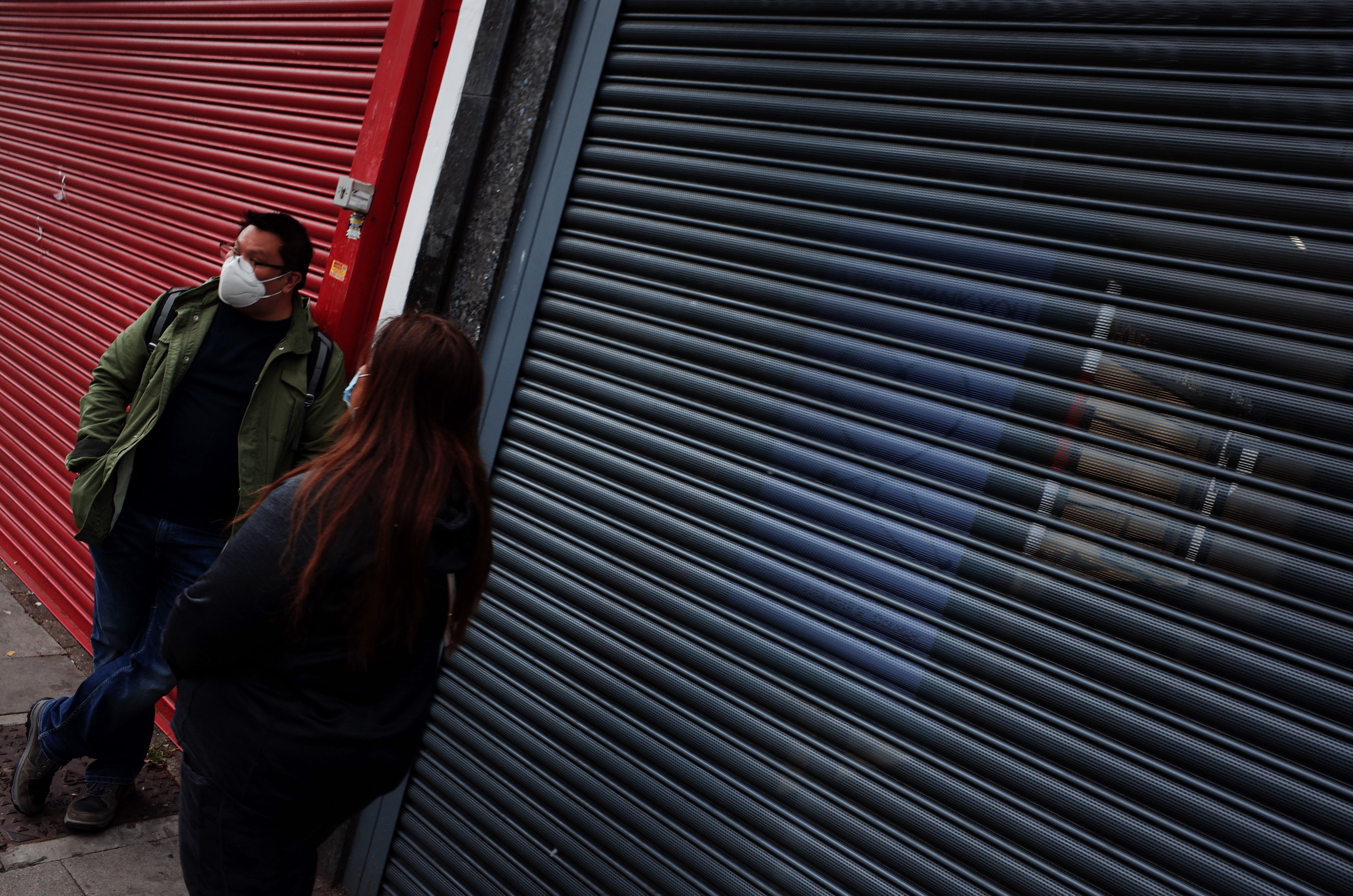 People wearing face masks stand beside shuttered stores on Kilburn High Road in London, England, on June 7, 2020. Covid-19 deaths across the UK now stand at 40,542 according to the daily tally from the Department of Health and Social Care, including an additional 77 deaths added today. (Photo by David Cliff/NurPhoto via Getty Images)